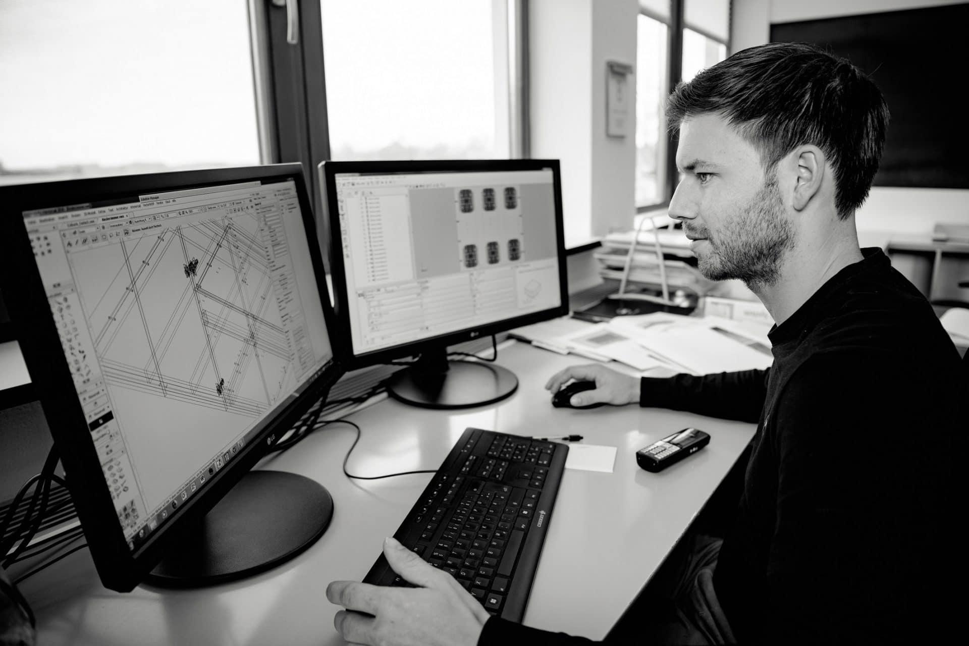 Konstrukteur sitzt vor einem Computer und entwirft eine Einbaulösung - Bild schwarz-weiß
