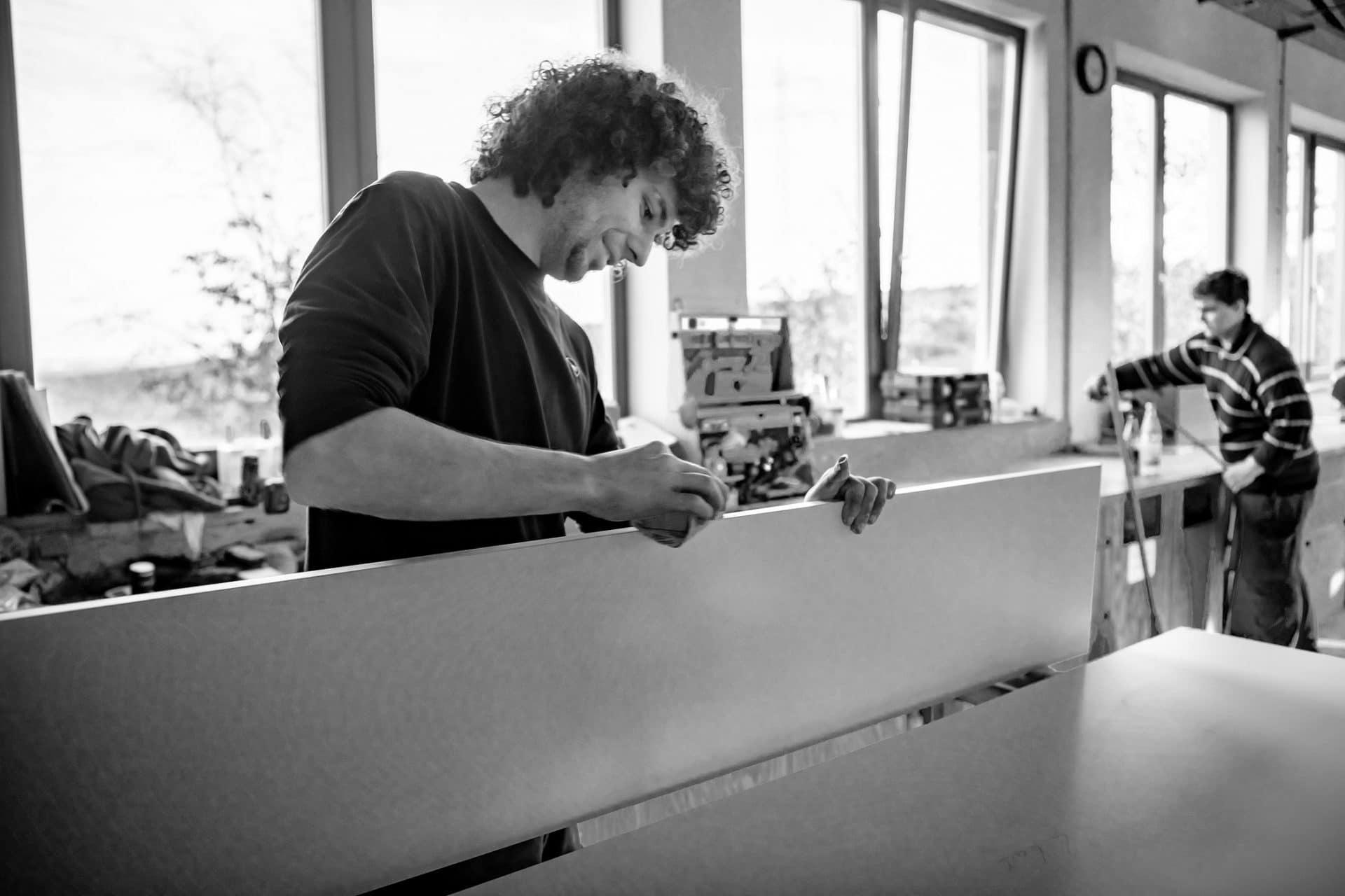 Schreiner schleift ein Werkstück ab in der Schreinerei - Bild in schwarz-weiß