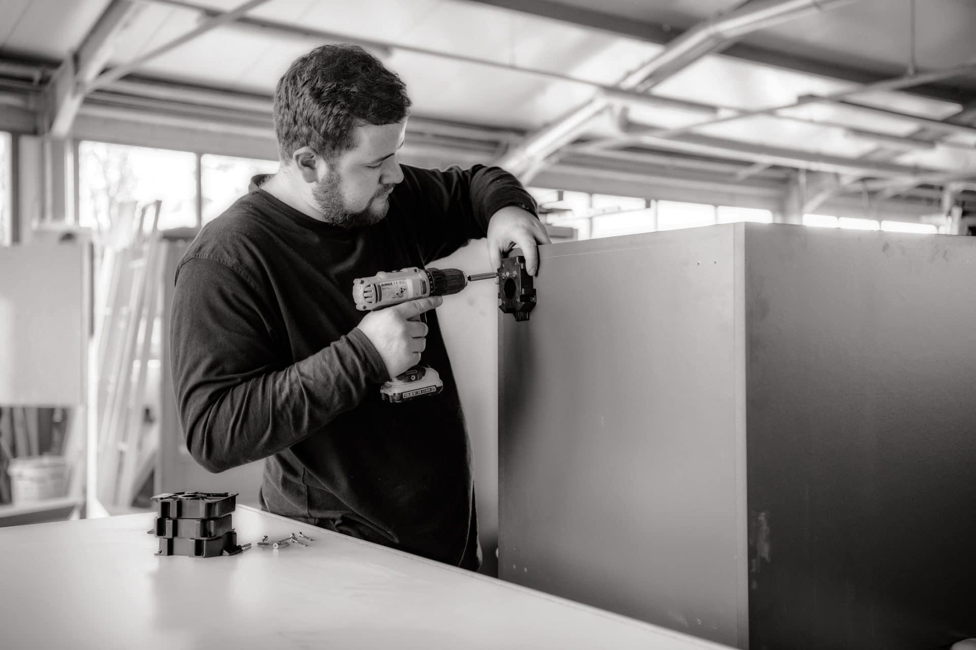 Ein Schreiner montiert Standfüße an ein Werkstück in der Schreinerei VOIT mit einem Akkuschrauber - Bild in schwarz-weiß