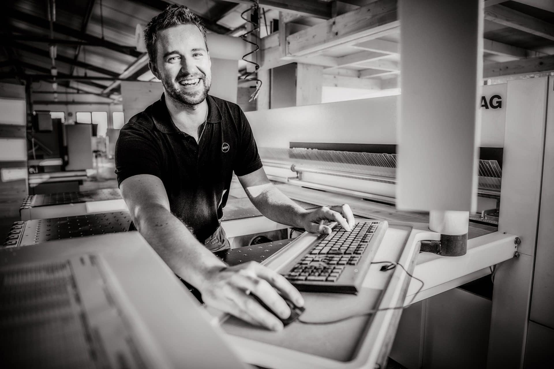 Schreiner bedient eine Verarbeitungsmaschine in der Schreinerei VOIT - Bild schwarz-weiß