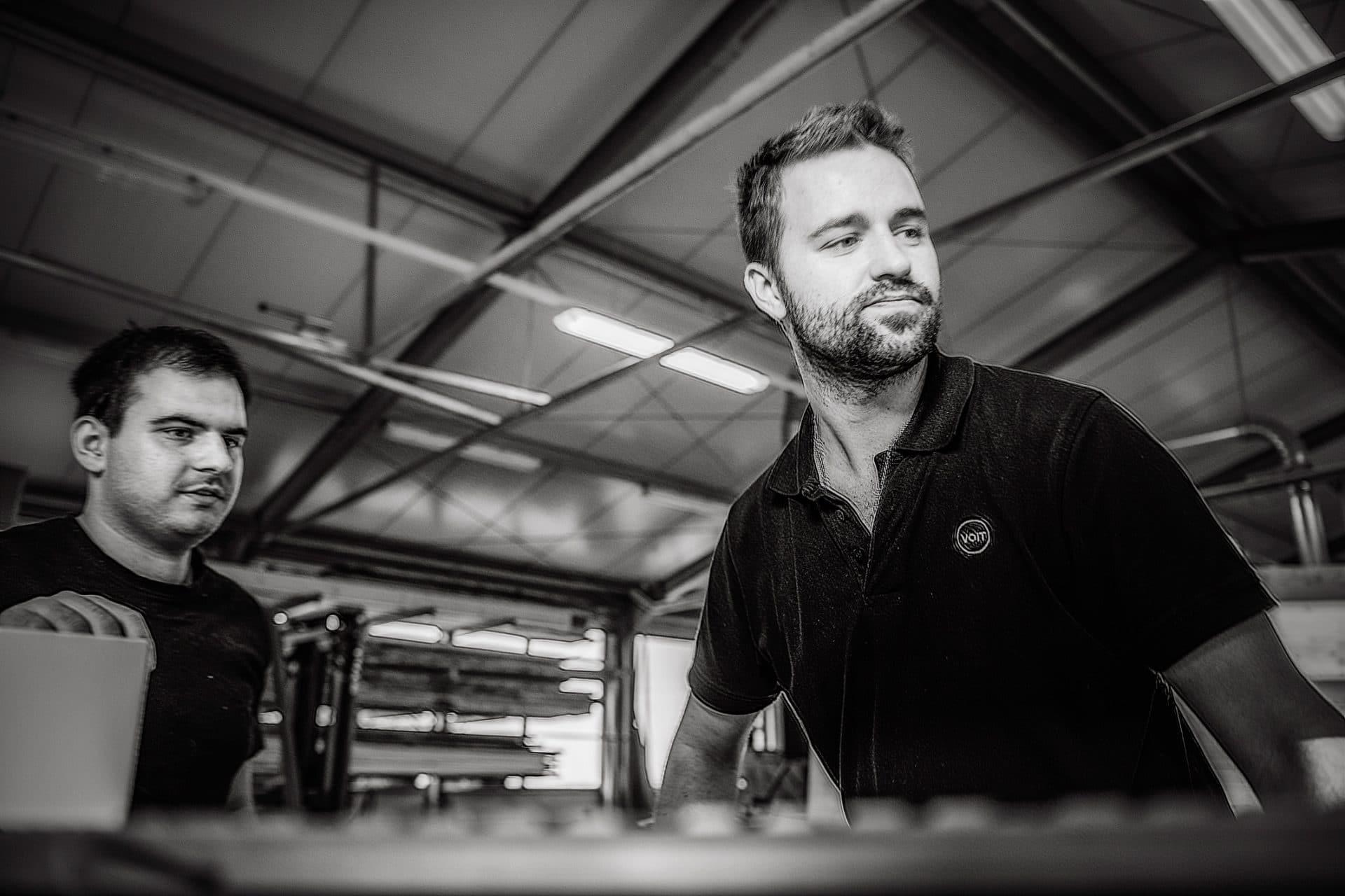 Zwei Schreiner planen die nächsten Fertigungsschritte an einer Maschine in der Schreinerei VOIT - Schwarz-weiß Bild