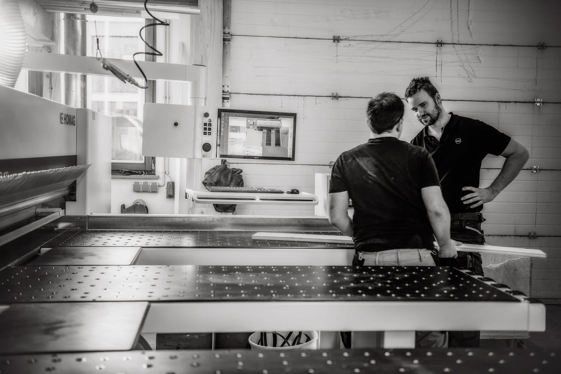Zwei Schreiner legen ein Werkstück in eine HOMAG Verarbeitungsmaschine ein - Bild schwarz-weiß