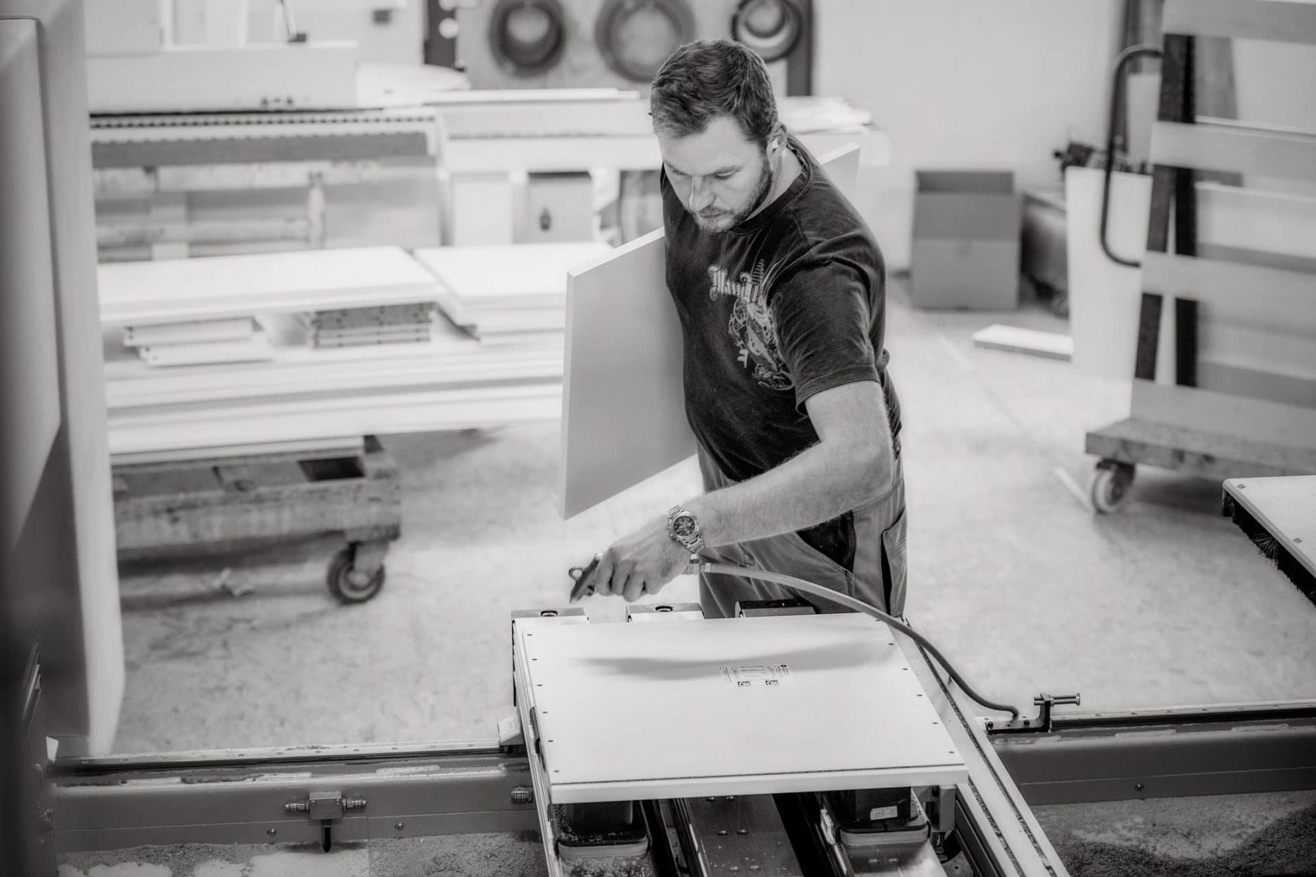 Schreiner bedient eine Verarbeitungsmaschine in der Schreinerei VOIT