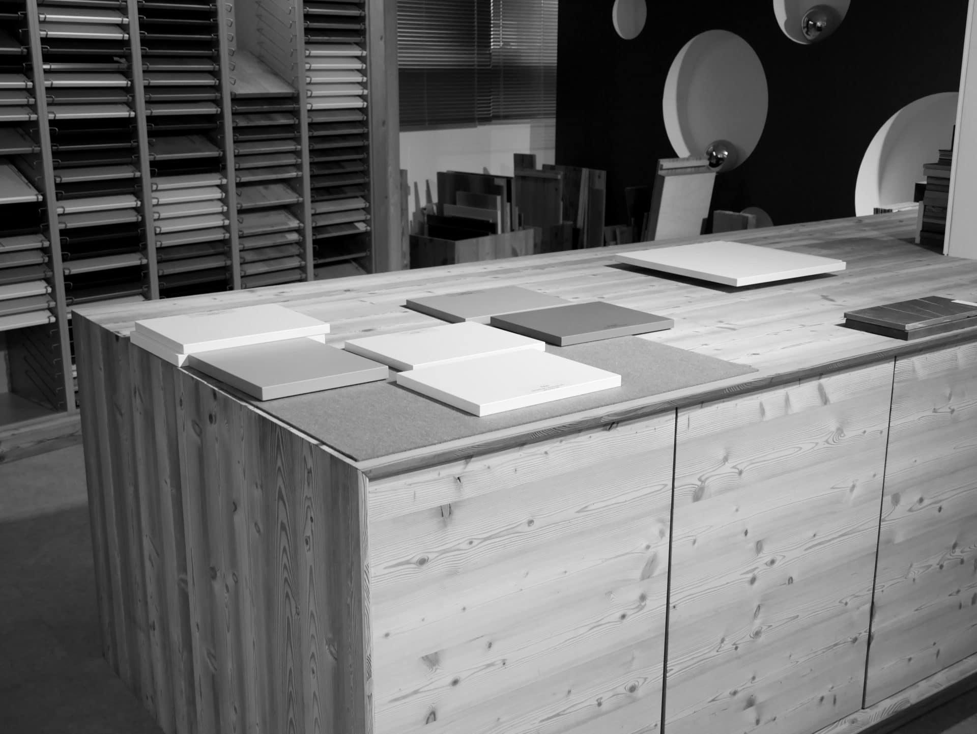Showroom von Schreinerei und Planungsbüro VOIT in Markt Schwaben, Materialauswahlbereich mit verschiedensten Hölzern auf einem Tisch - Bild in schwarz-weiß