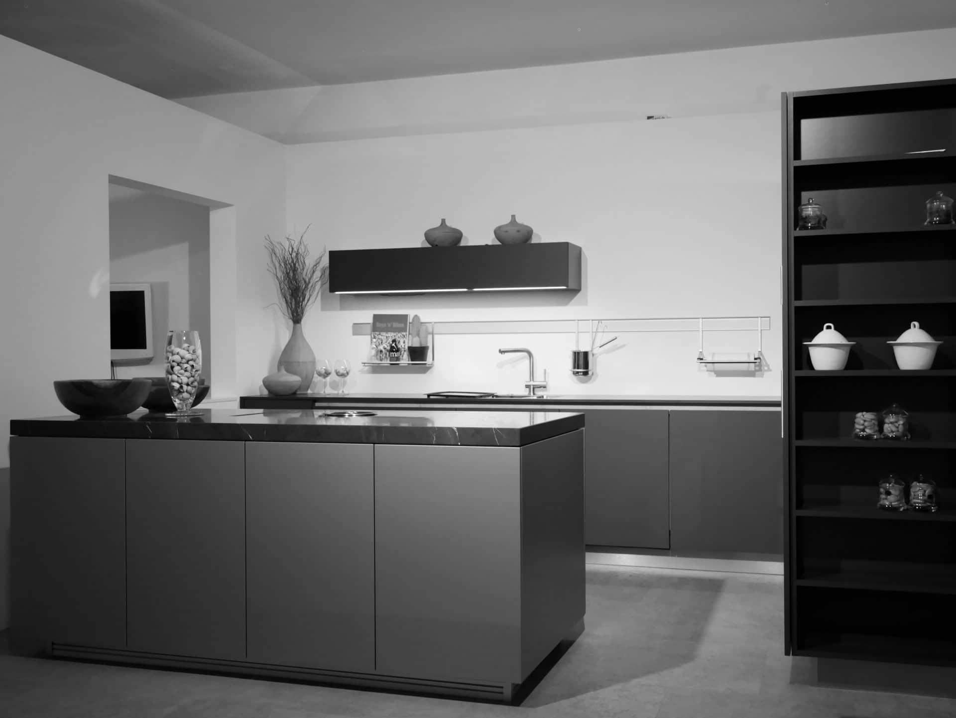 Showroom von Schreinerei und Planungsbüro VOIT in Markt Schwaben, Designerküche aus Naturstein mit Spühlbecken Amatur und Dekoration im Hintergrund - Bild in schwarz-weiß