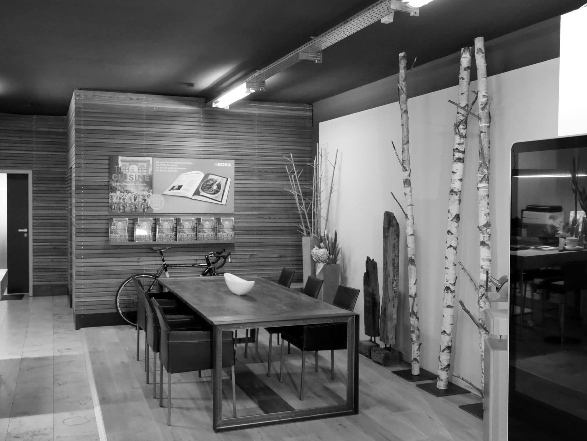 Showroom von Schreinerei und Planungsbüro VOIT in Markt Schwaben, Besprechungsbereich mit Tisch und 6 Stühlen, rechts vor der Wand Dekoration aus Holz - Bild in schwarz-weiß