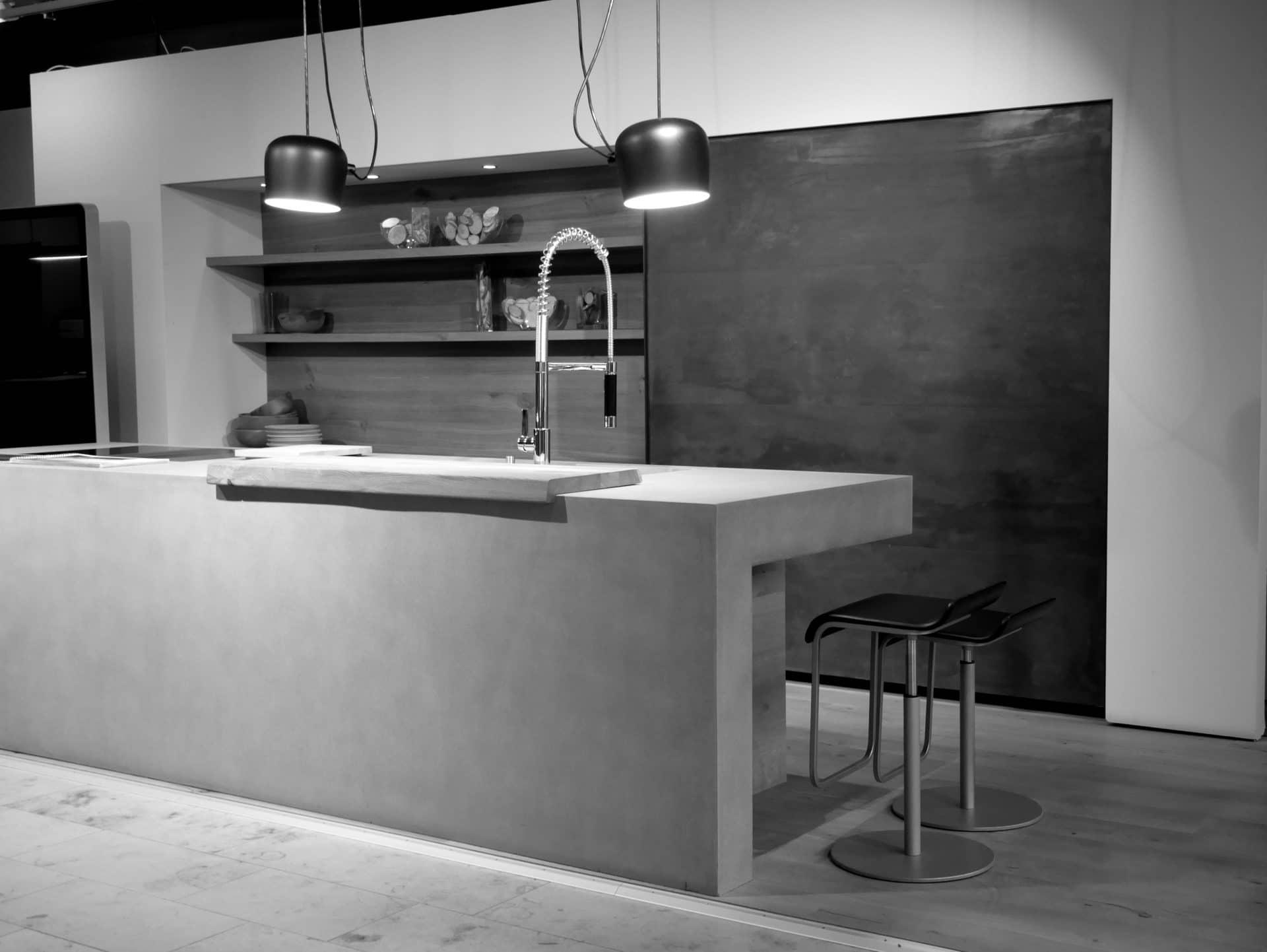 Showroom von Schreinerei und Planungsbüro VOIT in Markt Schwaben, Designerküche aus Beton mit Spühlbecken Amatur und zwei Barhockern - Bild in schwarz-weiß