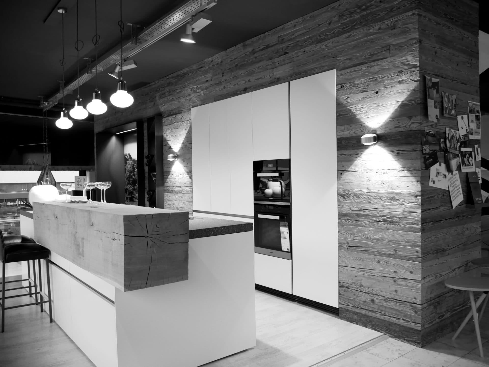 Showroom von Schreinerei und Planungsbüro VOIT in Markt Schwaben, Designerküche mit schwerer Anrichte aus Massivholz, im Hintergrund verschiedene Einbaugeräte - Bild in schwarz-weiß