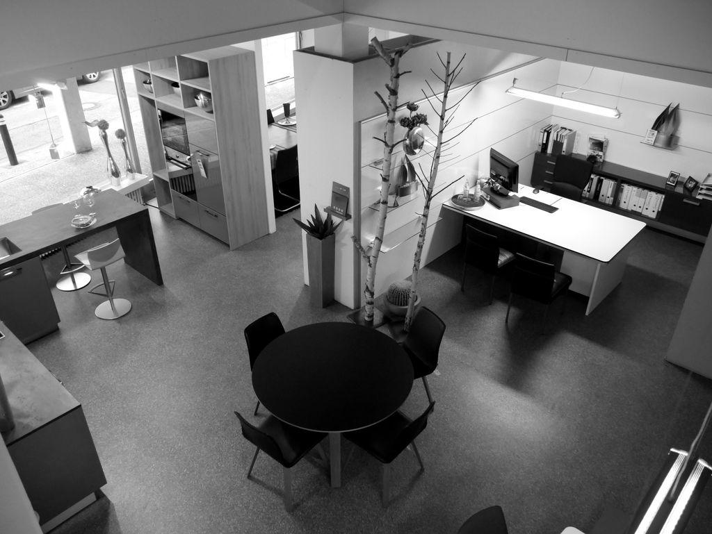 Showroom von Schreinerei und Planungsbüro VOIT in Markt Schwaben, Blick von oben auf den Besprechungsbereich, Schreibtische und Besprechungstisch mit vier Stühlen in Schwarz - Bild in schwarz-weiß