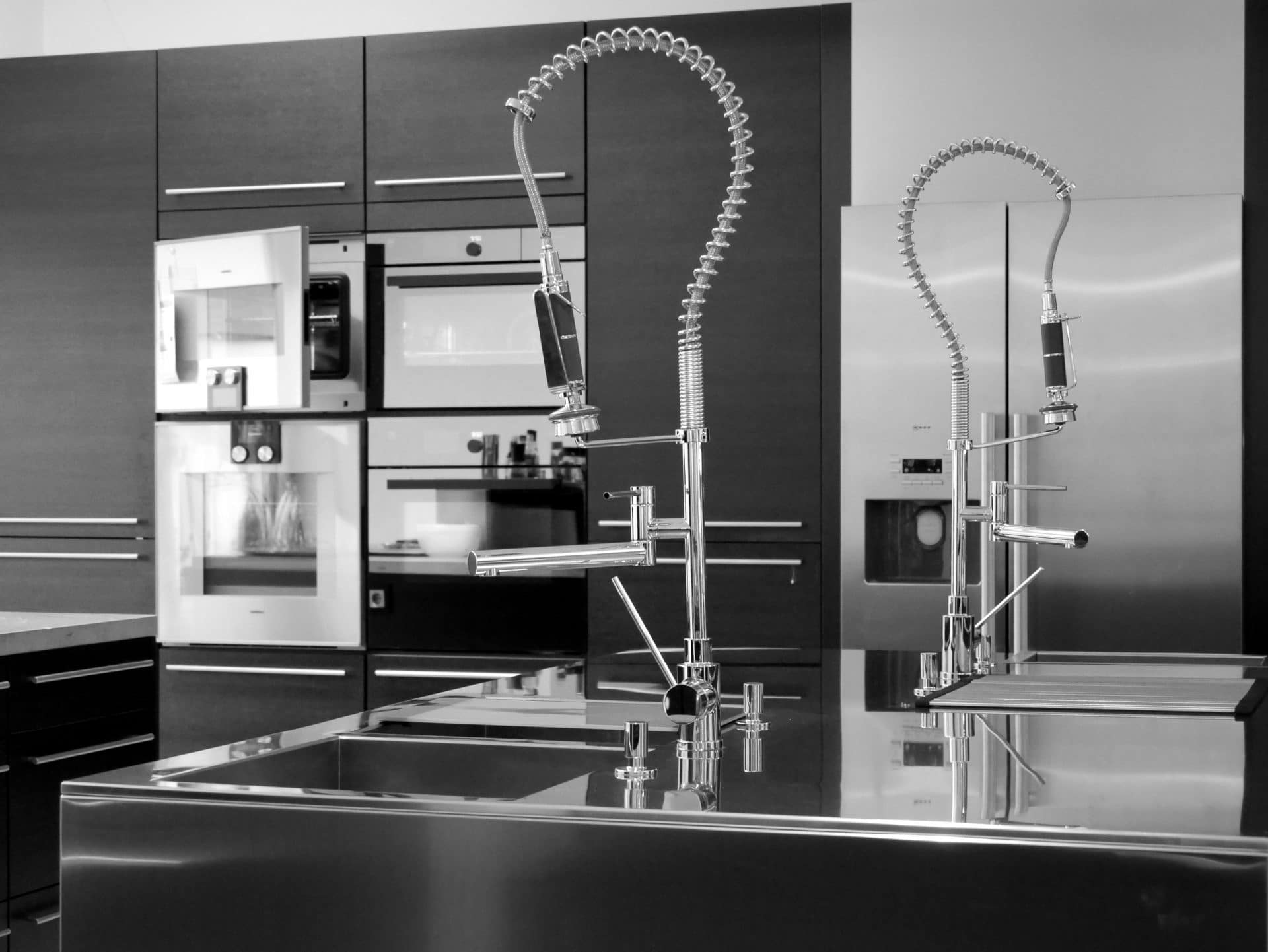 Showroom von Schreinerei und Planungsbüro VOIT in Markt Schwaben, Nahaufname von verschiedenen Spühlbecken mit Amaturen, im Hintergrund Einbaugeräte Lösungen - Bild in schwarz-weiß