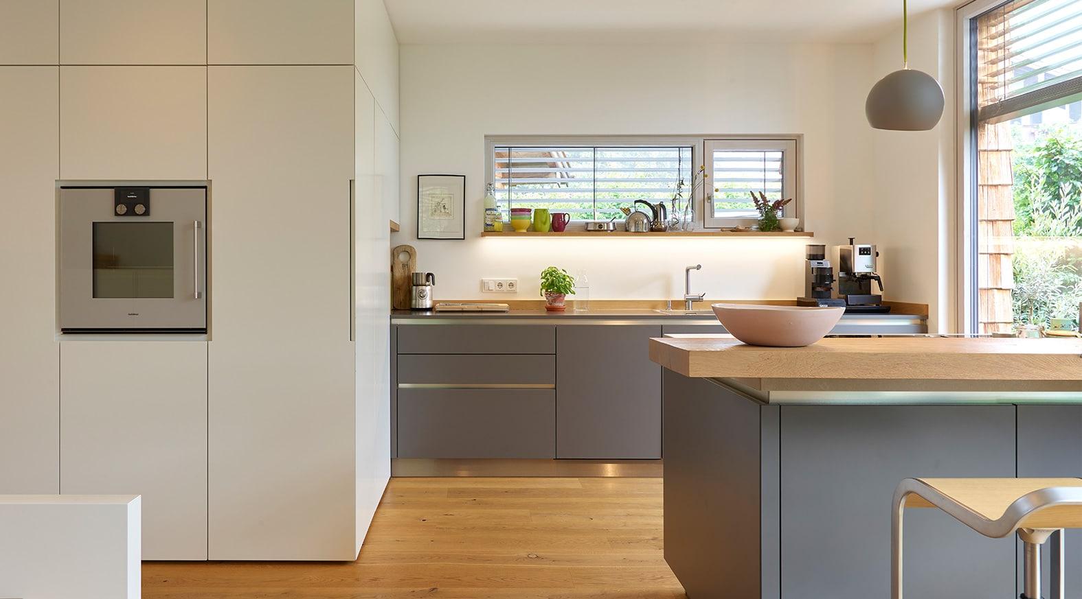 Küchendesign von VOIT aus Beton in Kombination mit MDF Fronten und Regalen in weiß