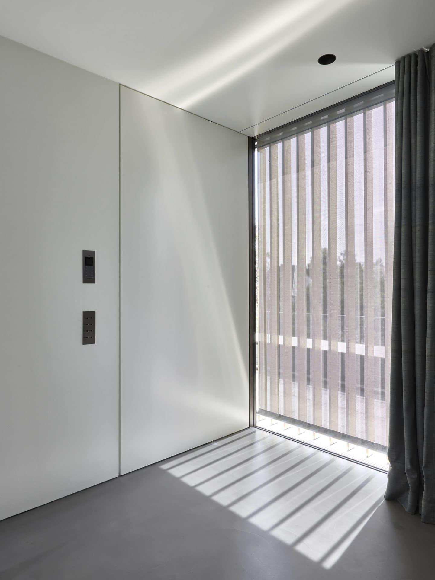 Küchendesign von VOIT aus geräucherter Eiche, Beton und Edelstahl - Badezimmertür geschlossen mit weißer Mattlack Front