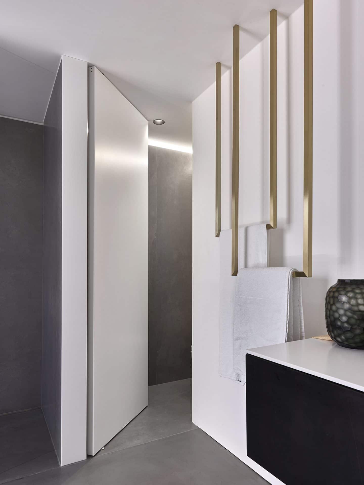 Küchendesign von VOIT aus geräucherter Eiche, Beton und Edelstahl - Badezimmertür geöffnet mit weißer Mattlack Front