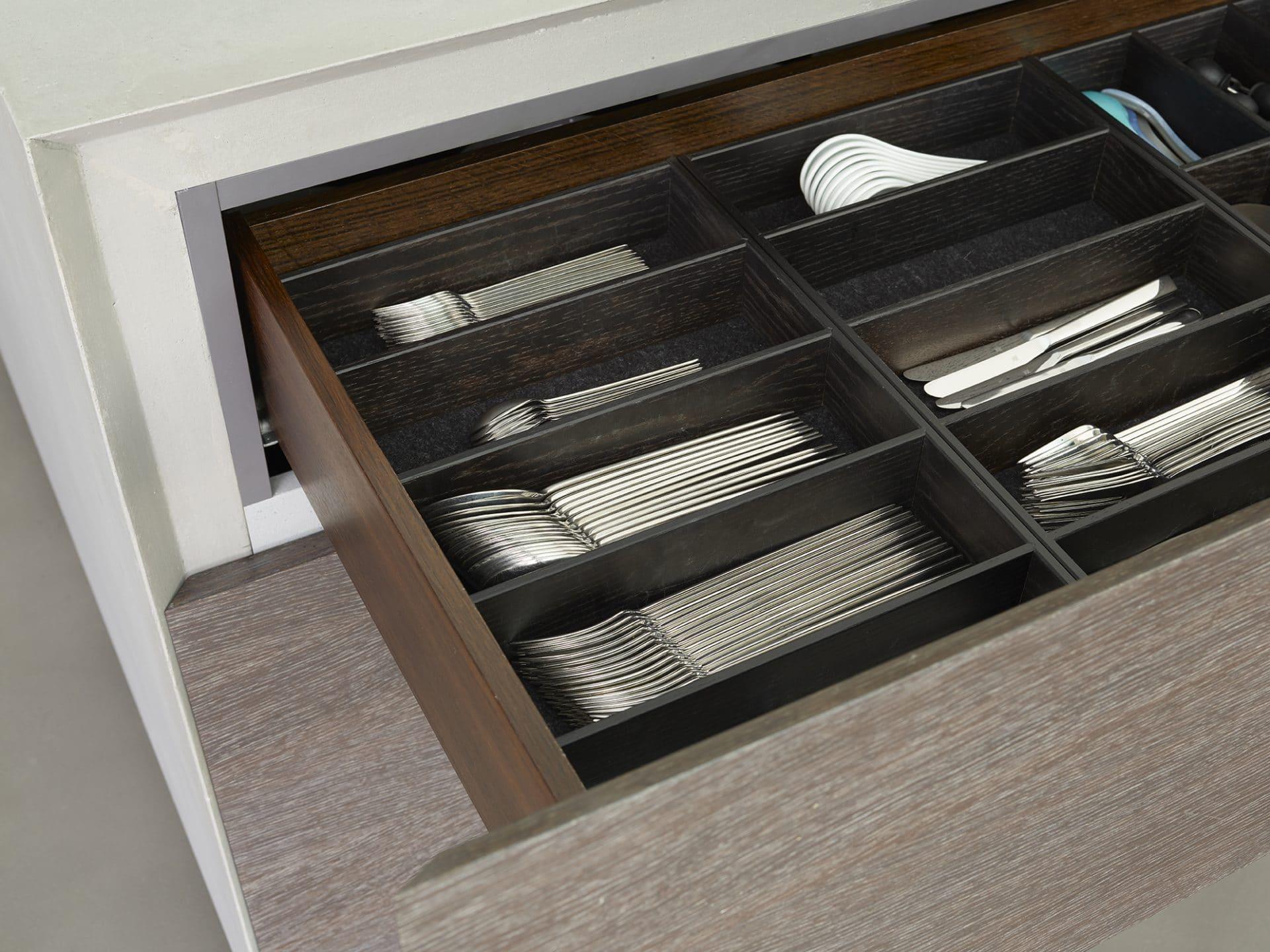 Küchendesign von VOIT aus geräucherter Eiche, Beton und Edelstahl - Besteckschubblade mit Besteck darin