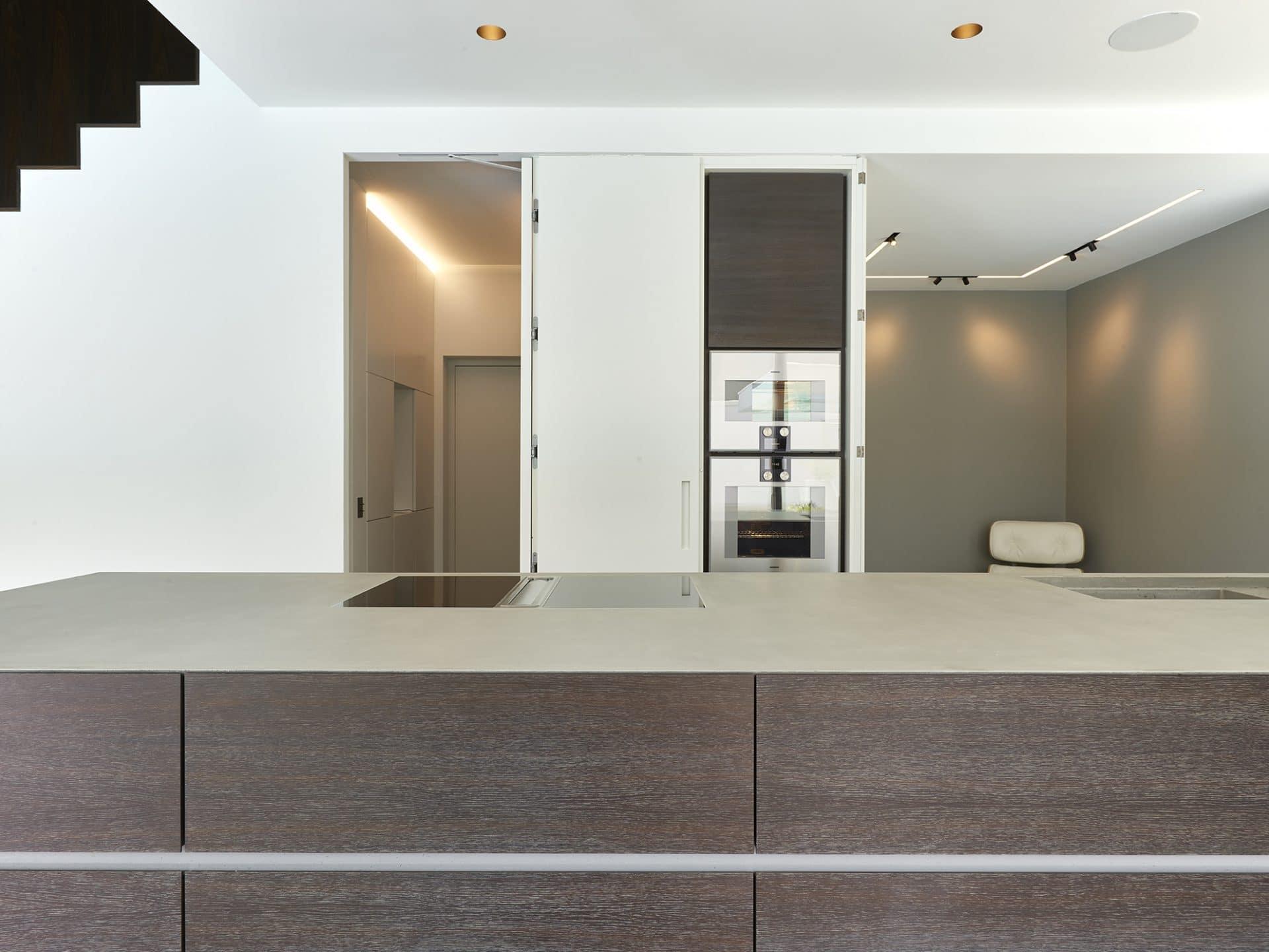 Küchendesign von VOIT aus geräucherter Eiche, Beton und Edelstahl - geöffnete Küchenzeile in Mattlack weiß mit Einbaugeräten, im Hintergrund ein Designerstuhl
