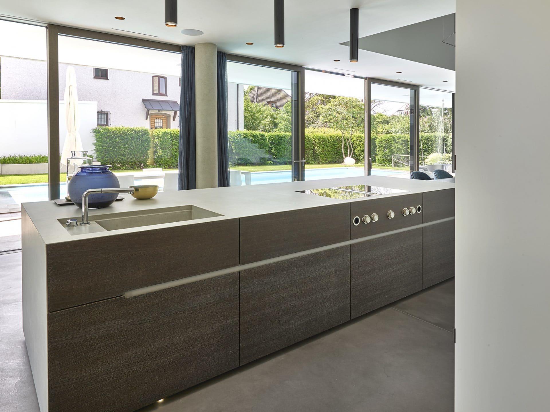 Küchendesign von VOIT aus geräucherter Eiche, Beton und Edelstahl - Blick in die Küche und den Garten mit Pool
