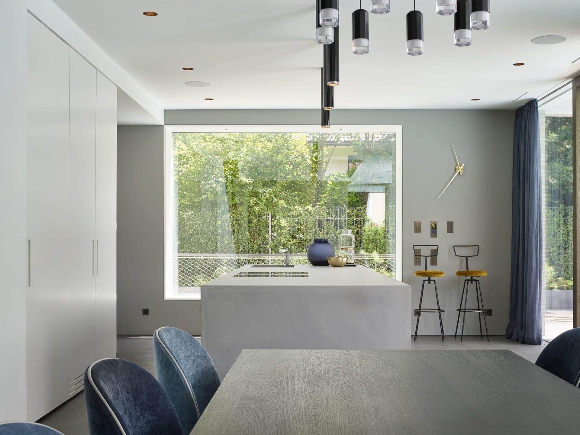 Küchendesign von VOIT aus geräucherter Eiche, Beton und Edelstahl - Kochinsel aus Beton, im Hintergrund 2 Designerstühle
