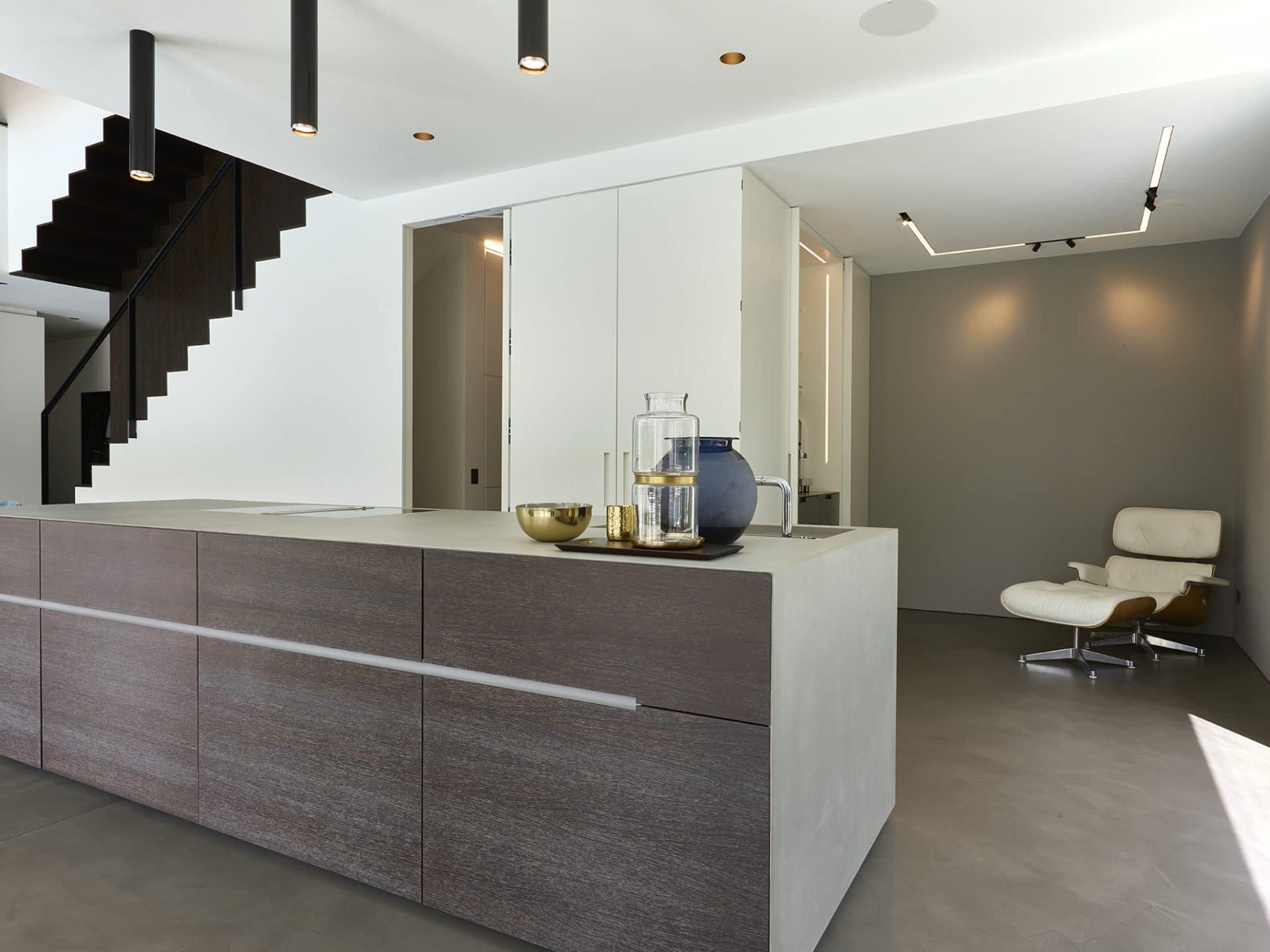 Küchendesign von VOIT aus geräucherter Eiche, Beton und Edelstahl - Versteckte Küchenzeile in Mattlack weiß, im Hintergrund ein Designerstuhl