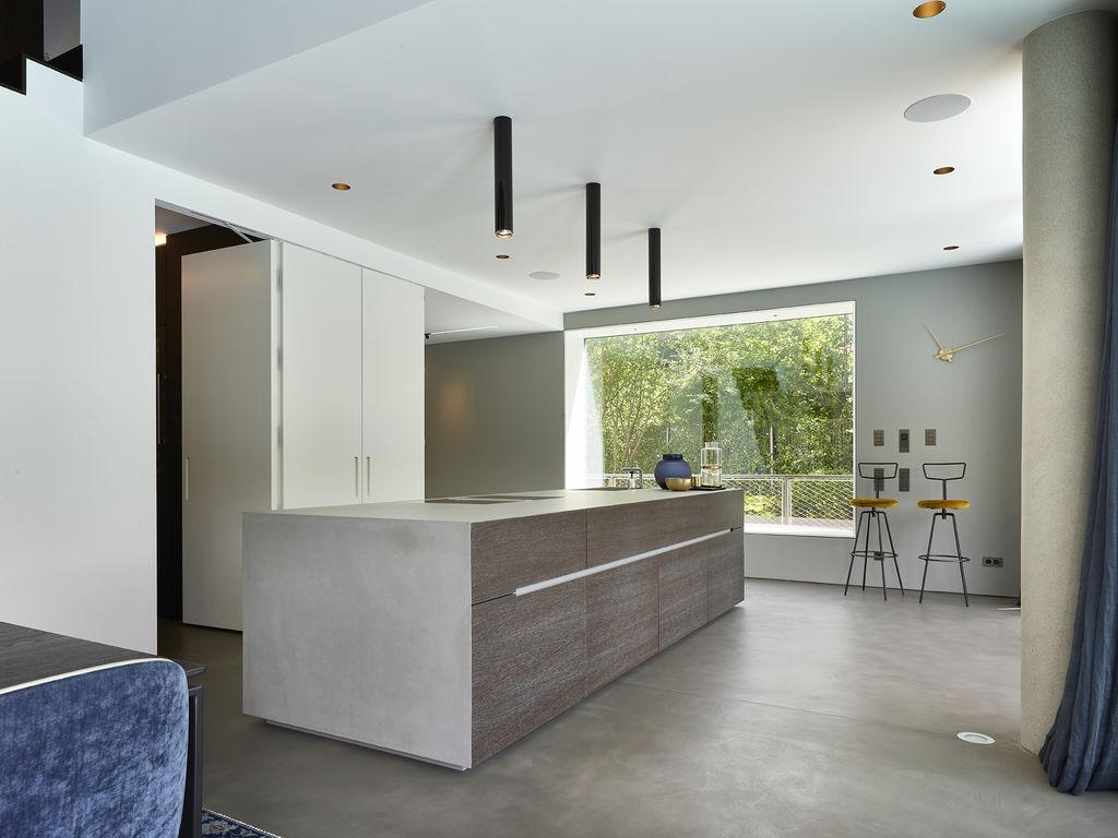 Küchendesign von VOIT aus geräucherter Eiche, Beton und Edelstahl - Versteckte Küchenzeile in Mattlack weiß, im Hintergrund zwei Designerstühle