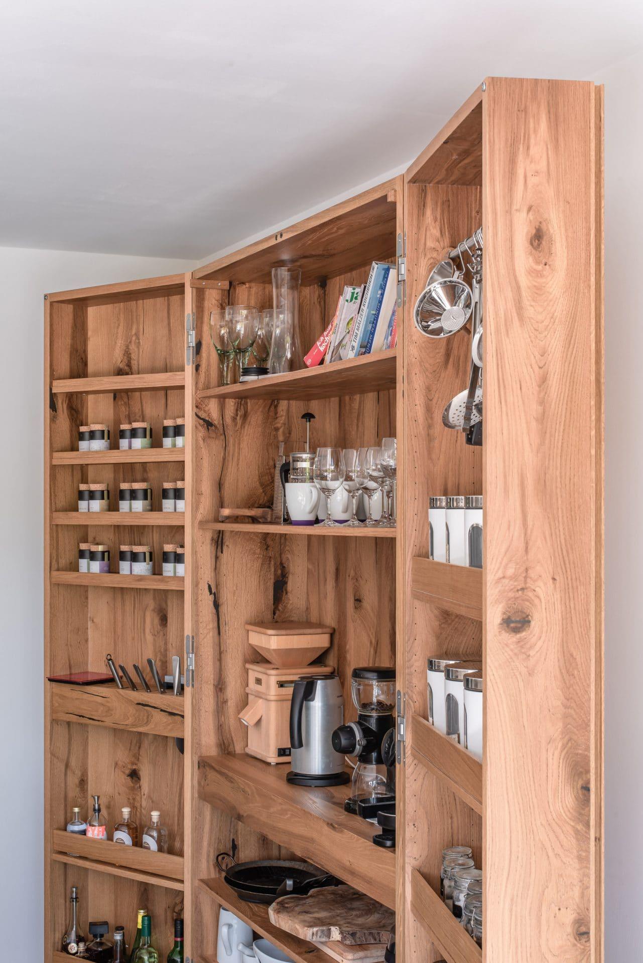 Küchendesign von VOIT aus rustikaler Eiche und Beton - Küchenschrank mit Gewürzen, Küchengeräten und Gläsern darin
