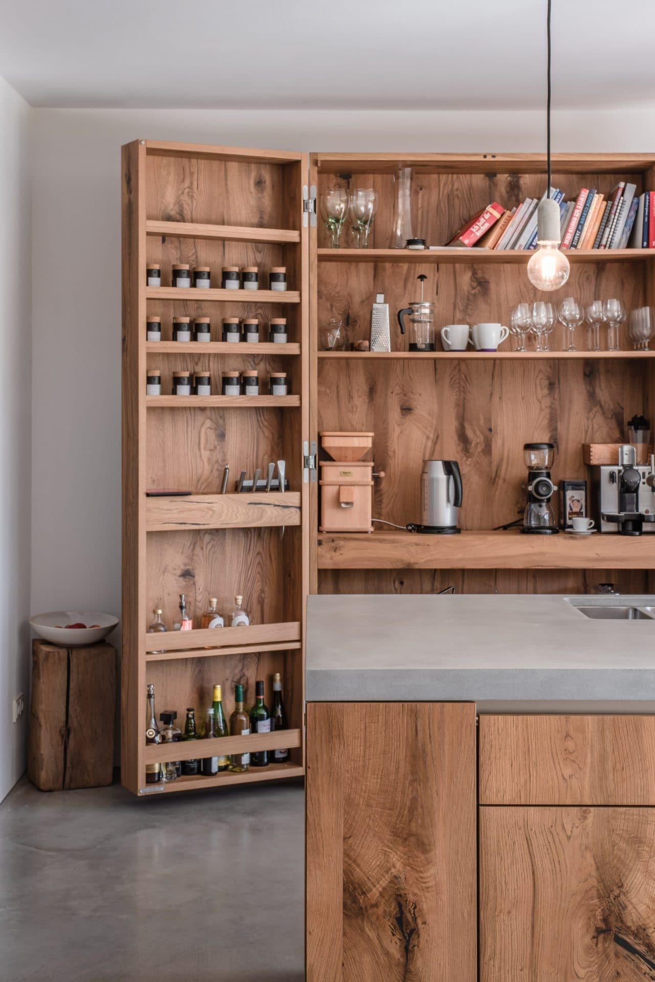 Küchendesign von VOIT aus rustikaler Eiche und Beton, im Hintergrund geöffnete Küchenschränke aus Eiche