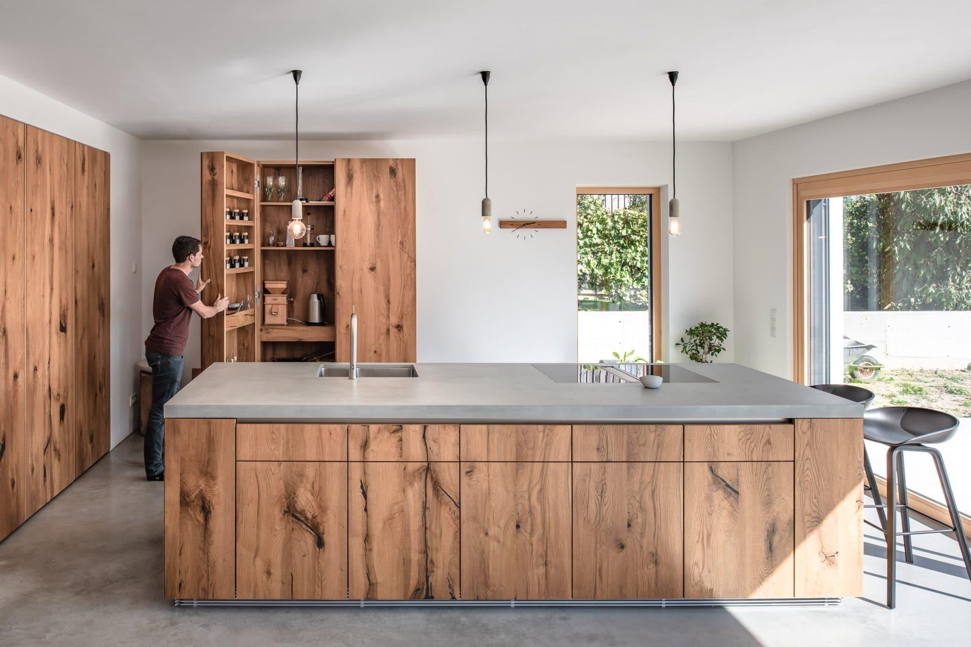 Küchendesign von VOIT aus rustikaler Eiche und Beton, im Hintergrund öffnet ein Mann Küchenschränke aus Eiche