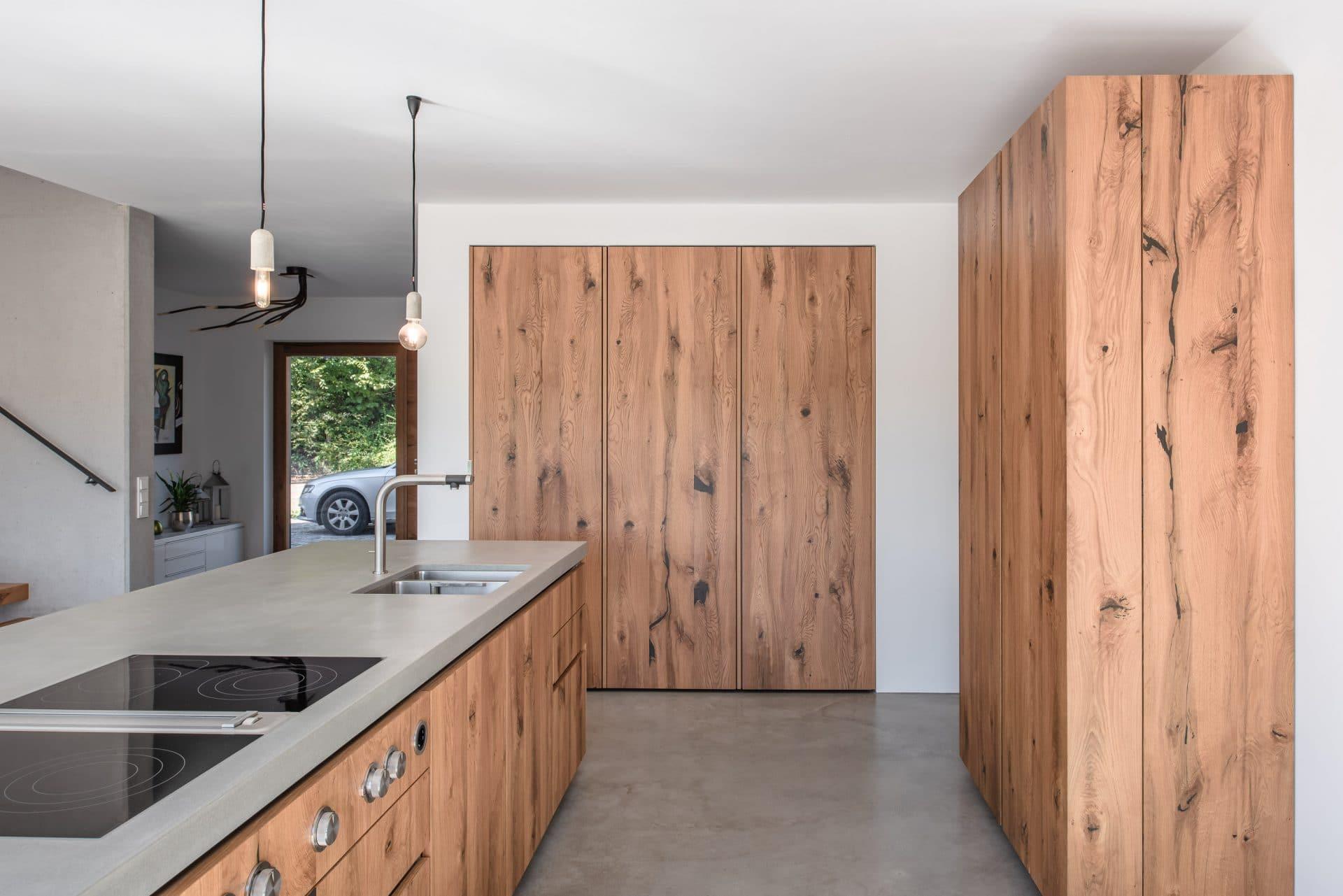 Küchendesign von VOIT aus rustikaler Eiche und Beton, im Hintergrund geschlossene Küchenschränke aus Eiche