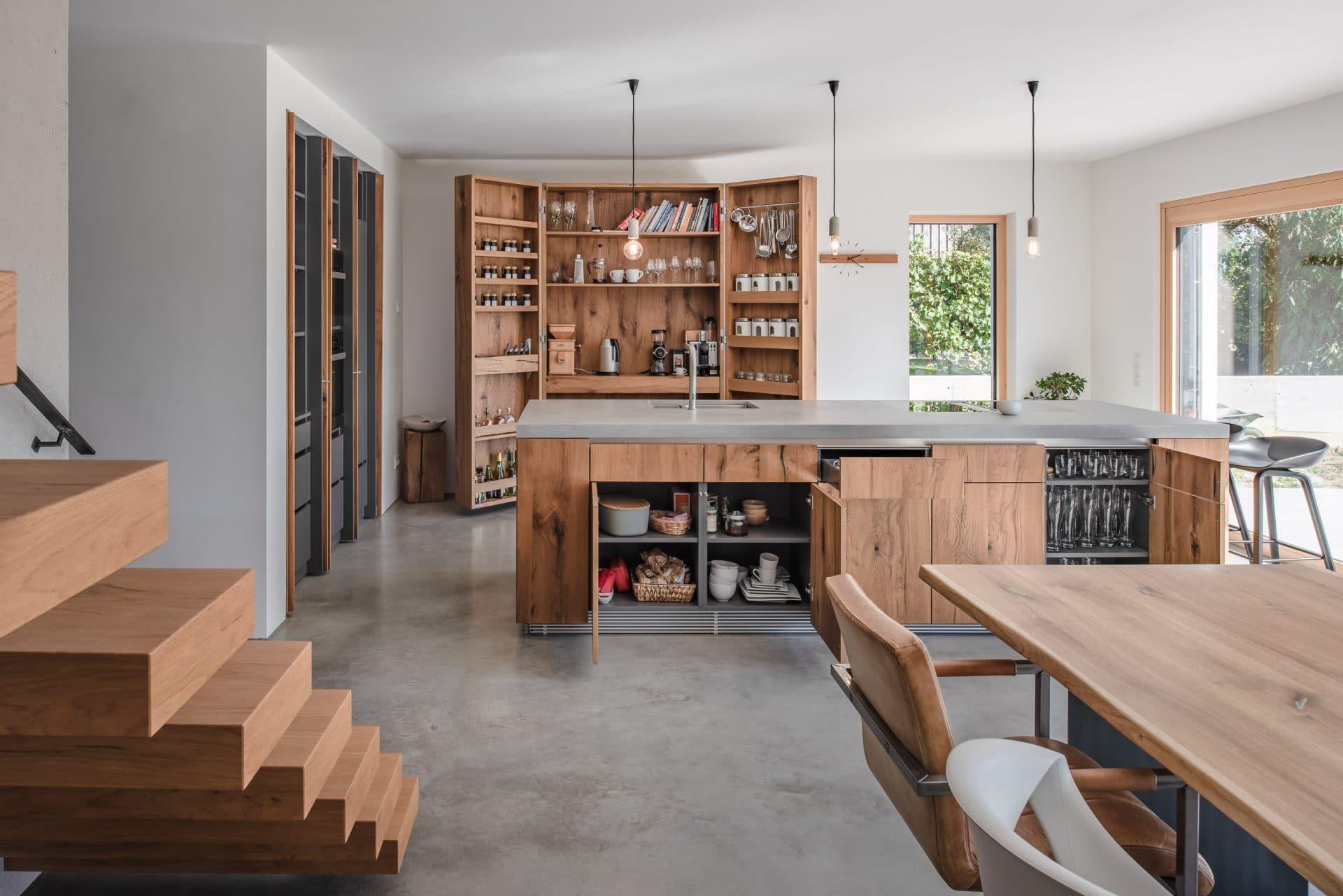 Küchendesign von VOIT aus rustikaler Eiche und Beton, im Hintergrund geöffnete Küchenschränke aus Eiche mit Gewürzen, Geschirr und weiteren Utensilien aus der Küche
