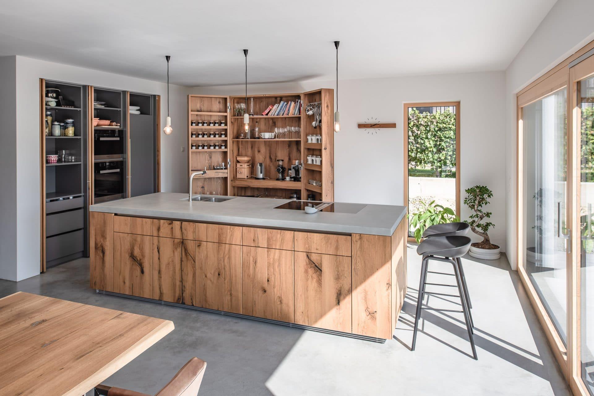 Küchendesign von VOIT aus rustikaler Eiche und Beton, im Hintergrund geöffnete Küchenschränke aus Eiche mit Einbaugeräten von Miele
