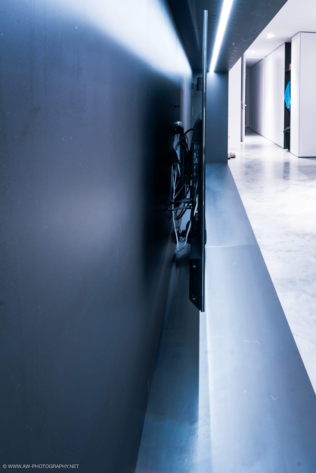 Innenausbau Penthousewohnung von VOIT in Schlichtstoff weiß und Stahl geschwärzt - Nahaufnahme von TV Regal mit geschwärztem Stahl als Hintergrund