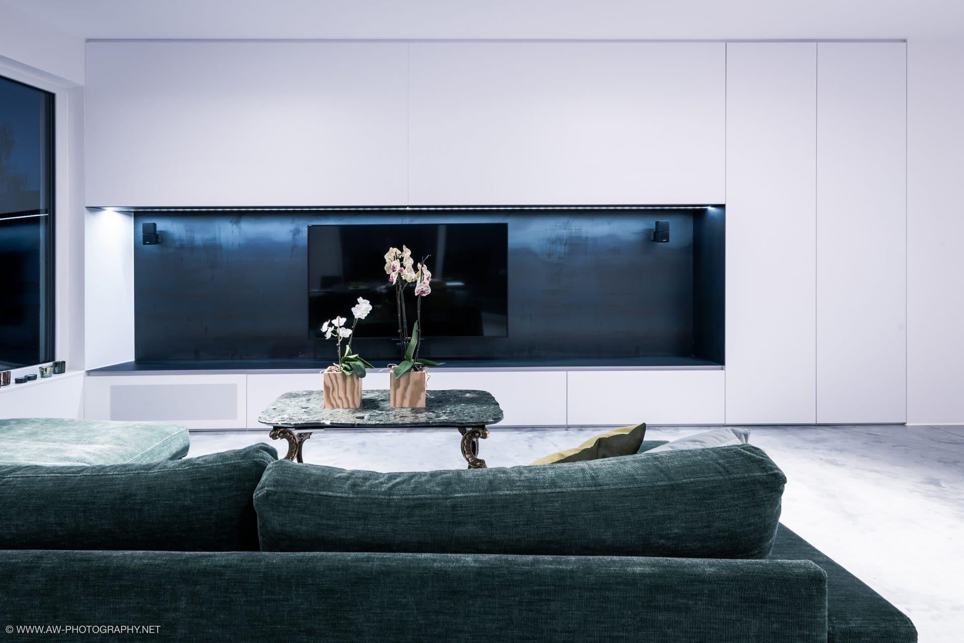 Innenausbau Penthousewohnung von VOIT in Schlichtstoff weiß und Stahl geschwärzt - Blick auf TV im Vordergrund ein Sofar und ein Designertisch