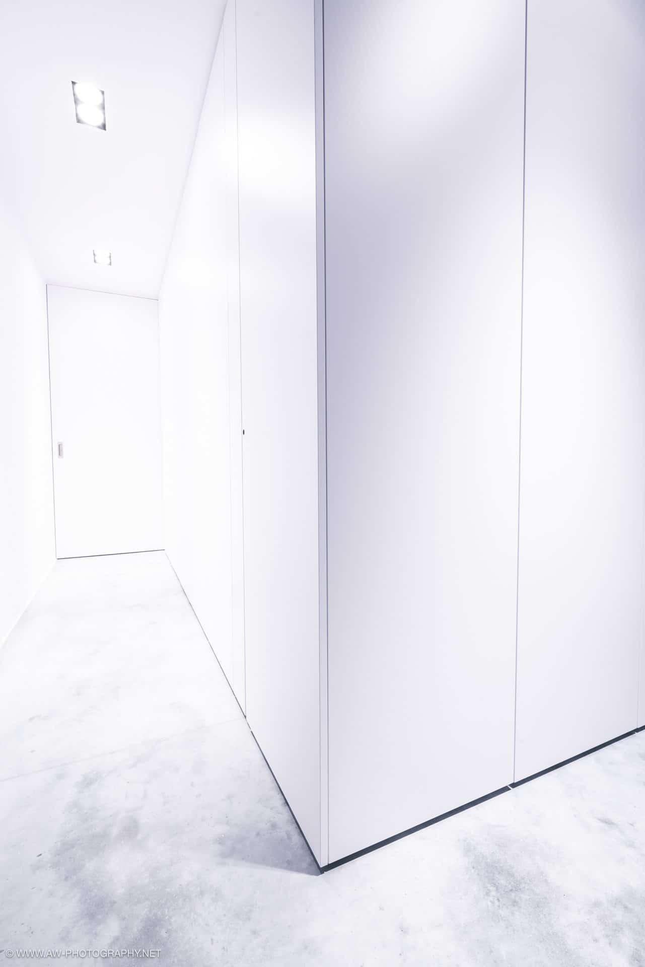 Innenausbau Penthousewohnung von VOIT in Schlichtstoff weiß und Stahl geschwärzt - Einbauschränke mit weißen Fronten und Beton Boden