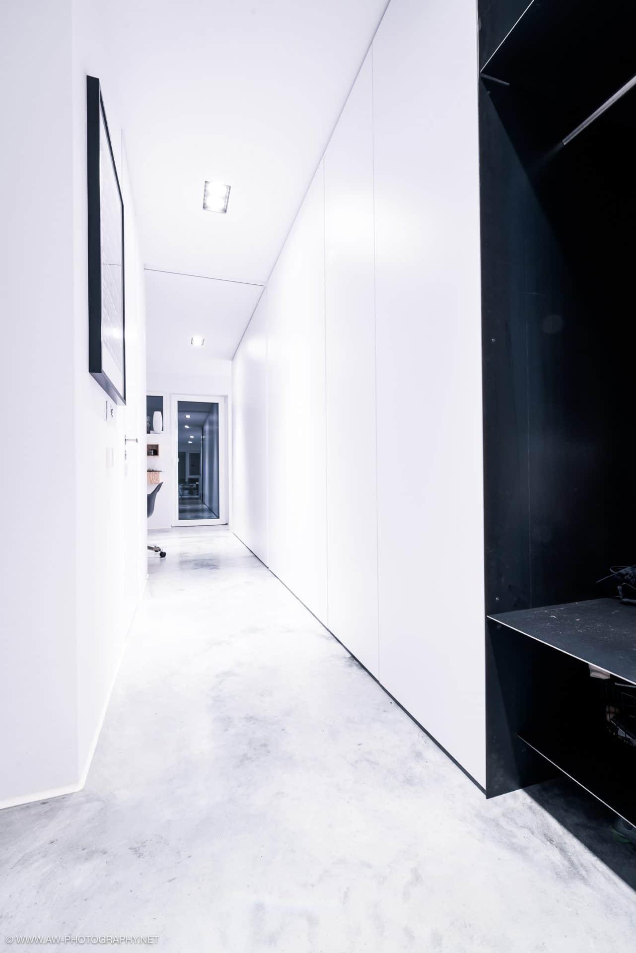 Innenausbau Penthousewohnung von VOIT in Schlichtstoff weiß und Stahl geschwärzt - Gang mit Garderobe