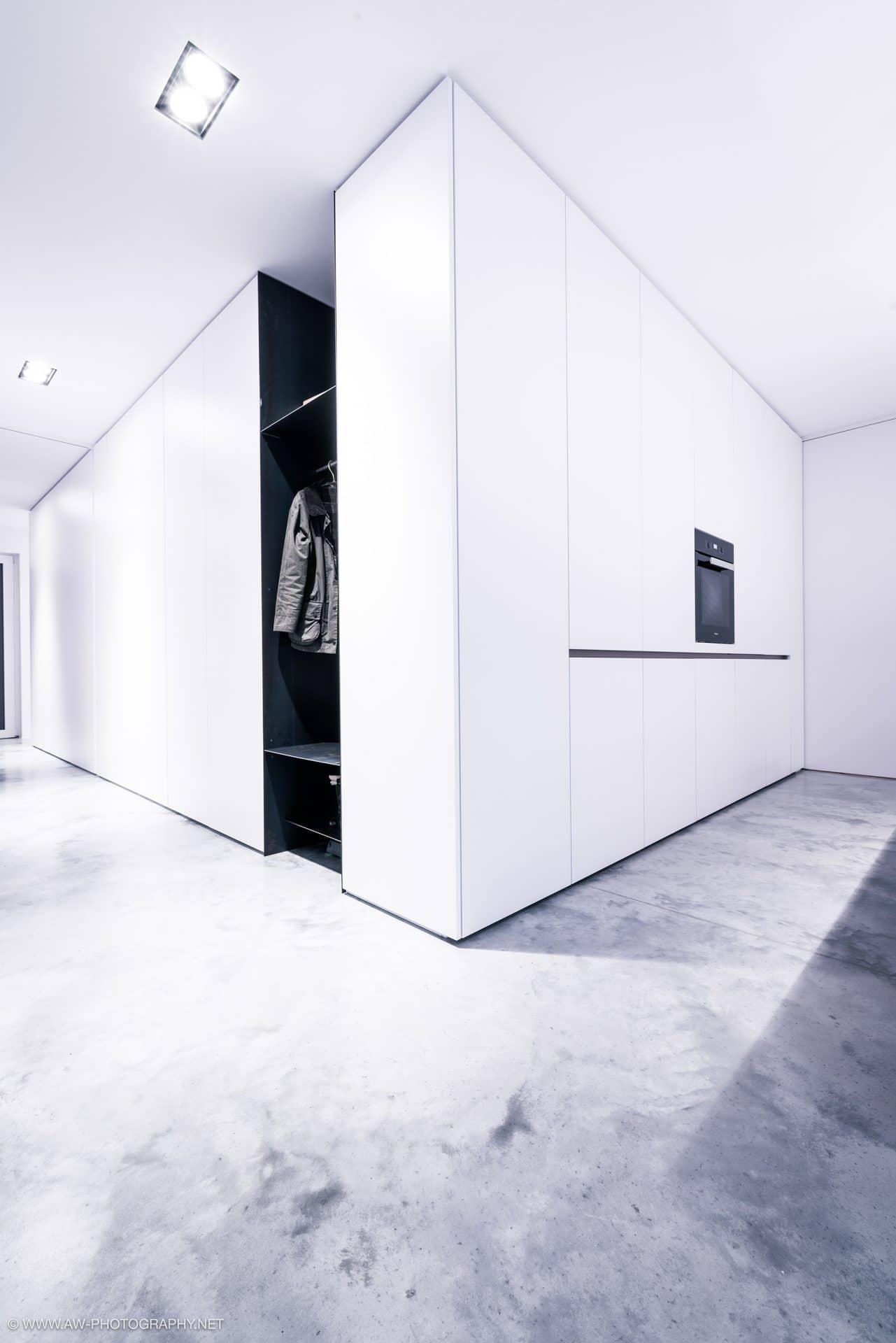 Innenausbau Penthousewohnung von VOIT in Schlichtstoff weiß und Stahl geschwärzt - Kücheneinbauten mit weißen Fronten und Blick in den Gang mit Garderobe