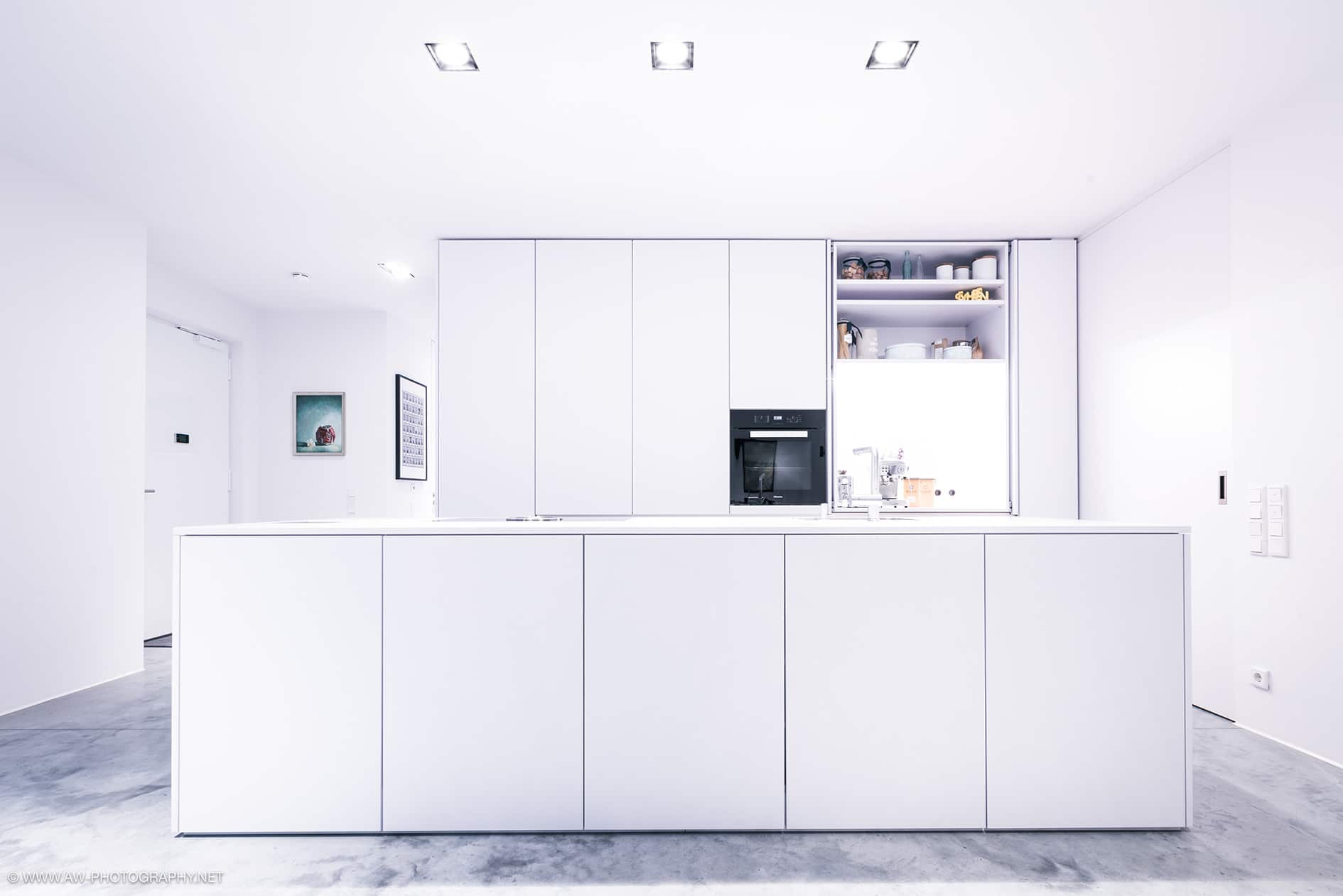 Innenausbau Penthousewohnung von VOIT in Schlichtstoff weiß und Stahl geschwärzt - komplett weiße Kochinsel, im Hintergrund Einbauschränke mit Küchengeräten und Kaffeemaschine rechts