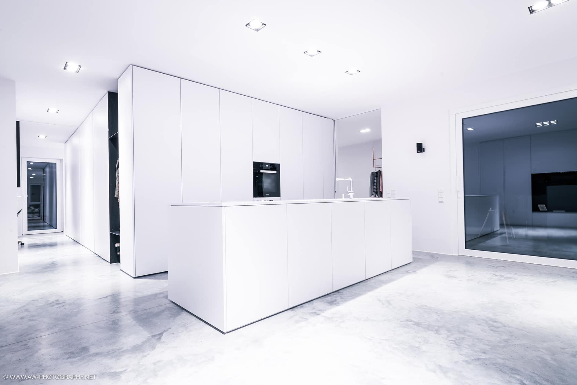 Innenausbau Penthousewohnung von VOIT in Schlichtstoff weiß und Stahl geschwärzt - Blick in die komplett weiße Küche, rechts großes Fenster zur Terrasse