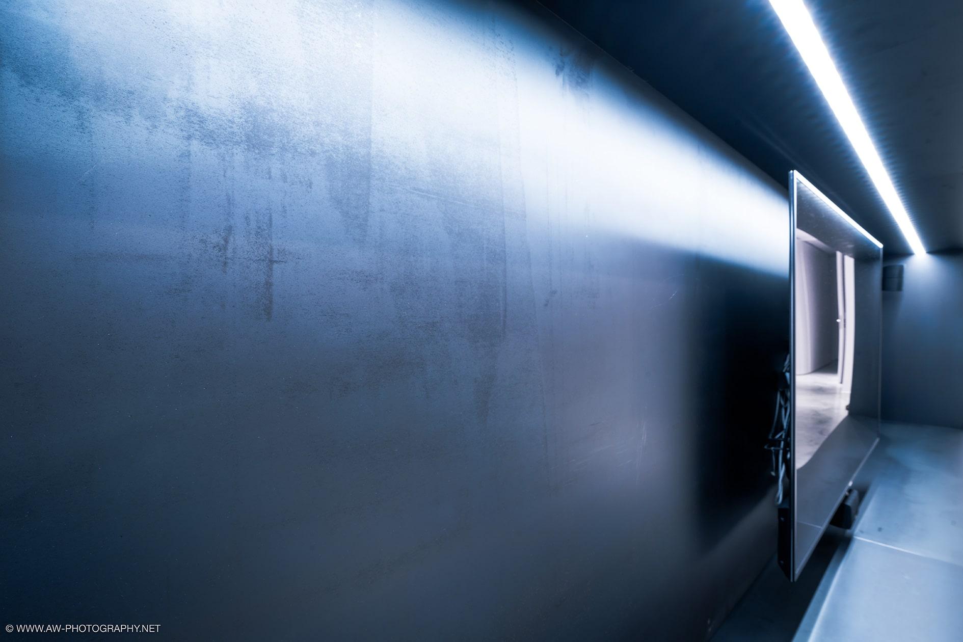 Innenausbau Penthousewohnung von VOIT in Schlichtstoff weiß und Stahl geschwärzt - Nahaufnahme TV Regal mit TV aus Stahl geschwärzt