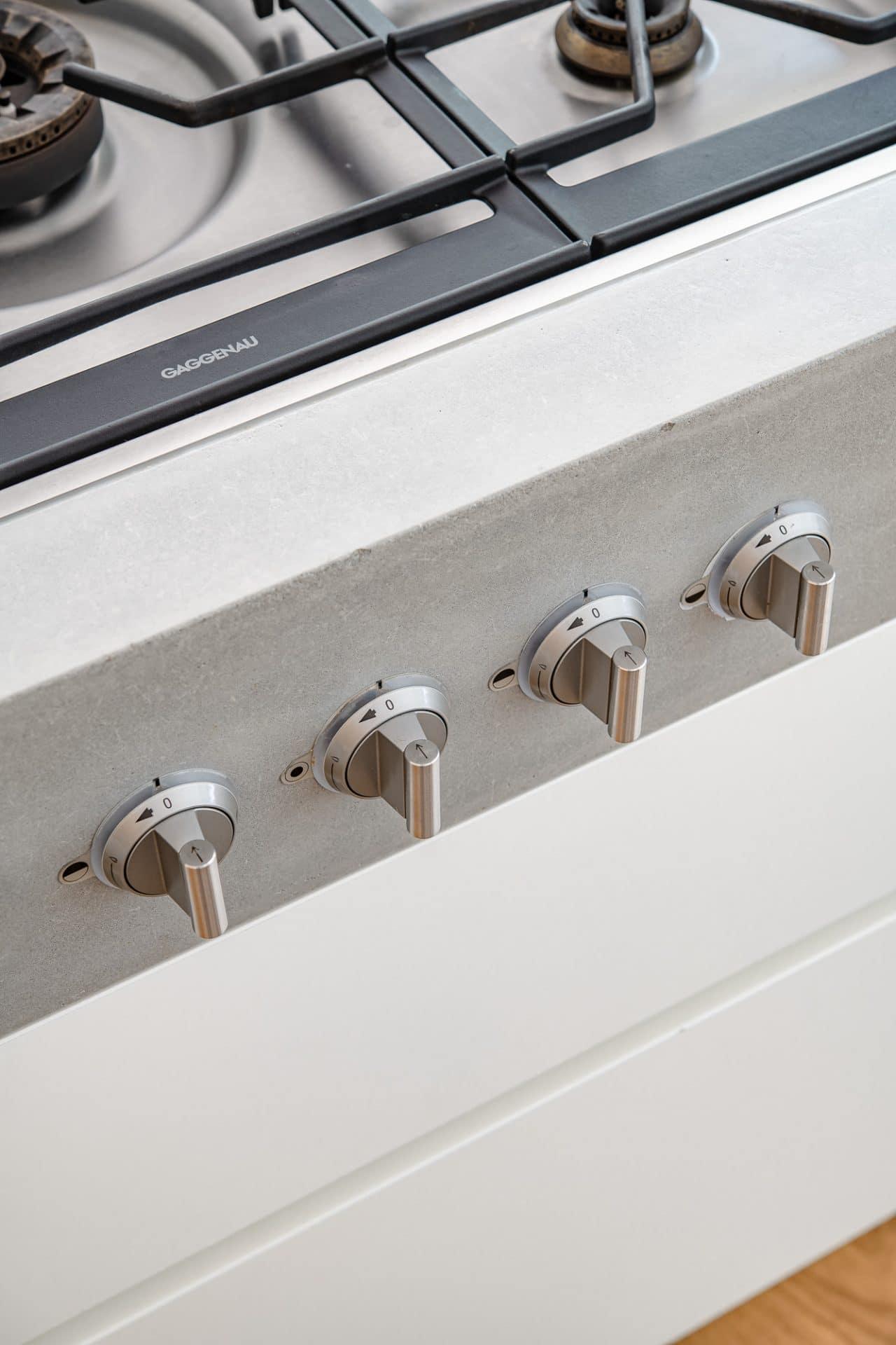 Küchendesign von VOIT aus Beton in Kombination mit Eiche Natur Fronten und Regalen, Nahaufnahme der Regler vom Gaggenau Gaskochfeld