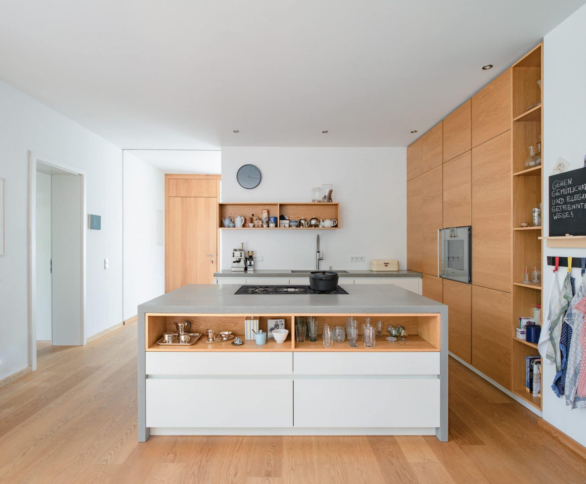 Küchendesign von VOIT aus Beton in Kombination mit Eiche Natur Fronten und Regalen mit Gaggenau Kochfeld und Herd