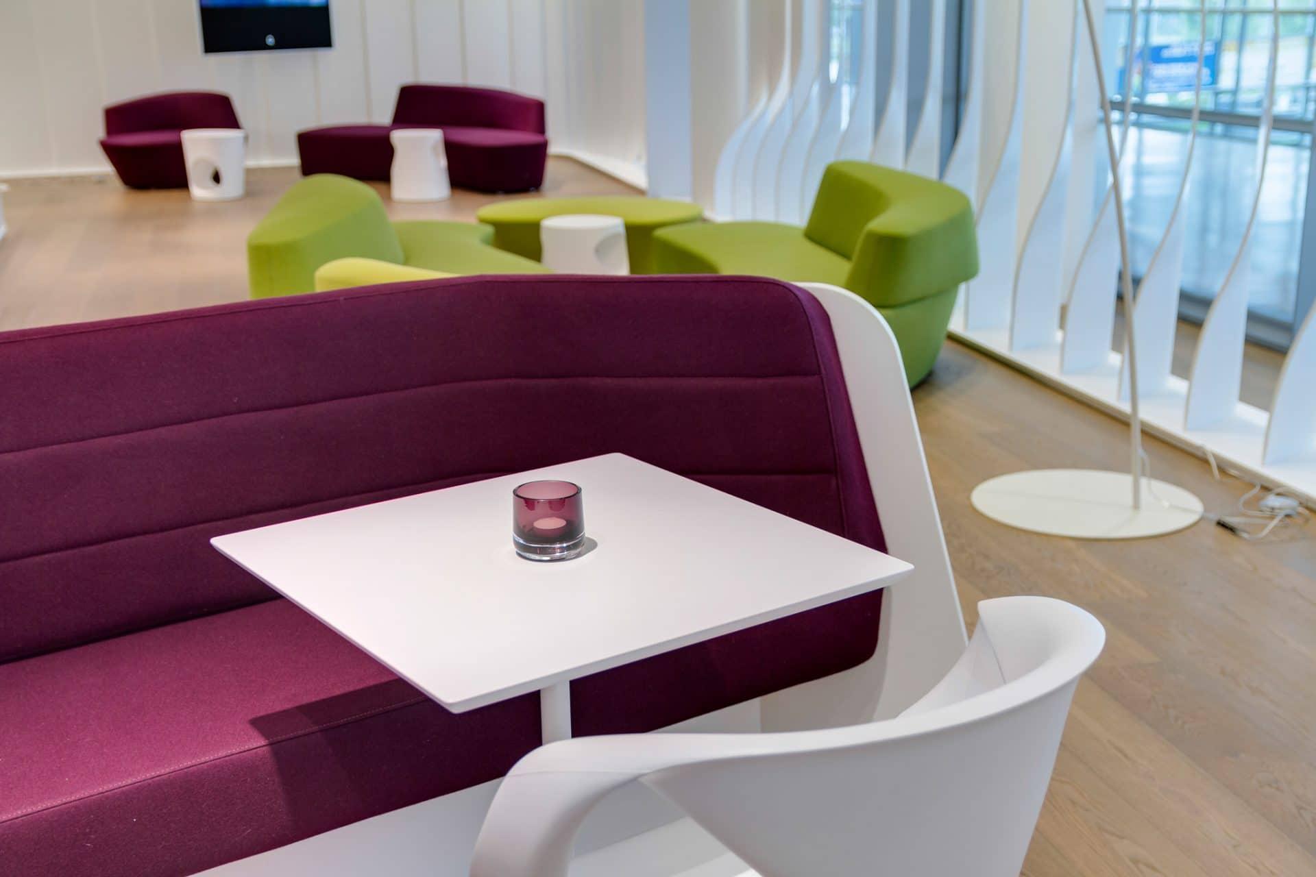 Bavaria Lounge in der Messe München, grüne und lila Sitzmöbel mit weißen Beistelltischen