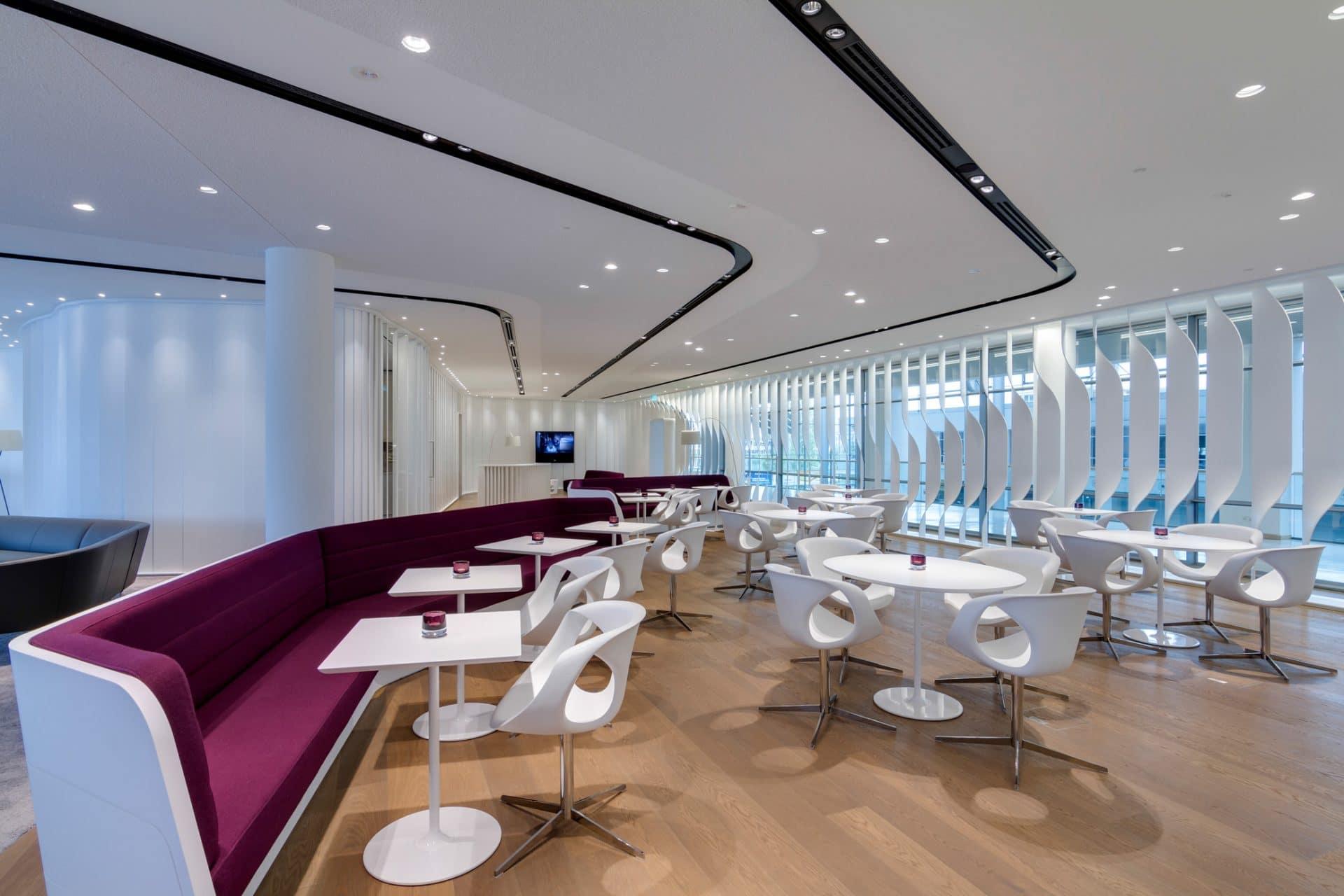 Bavaria Lounge in der Messe München, lila Sitzmöbel, weiße Beistelltische und weißer Sichtschutz an den Fenstern