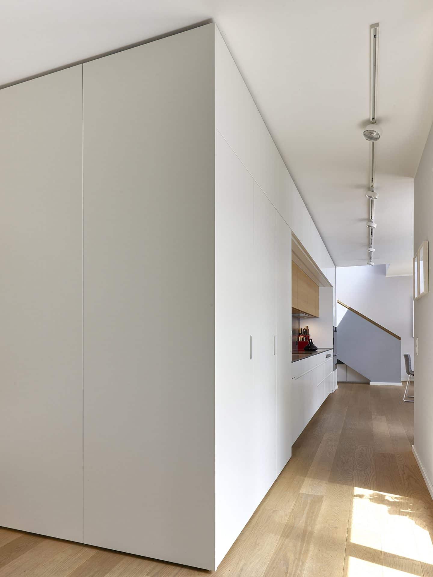 Inneneinrichtungsdesign von Voit, Küche mit weißen Fronten und schwarzer Arbeitsplatte - Blick in die Küche aus dem Gang