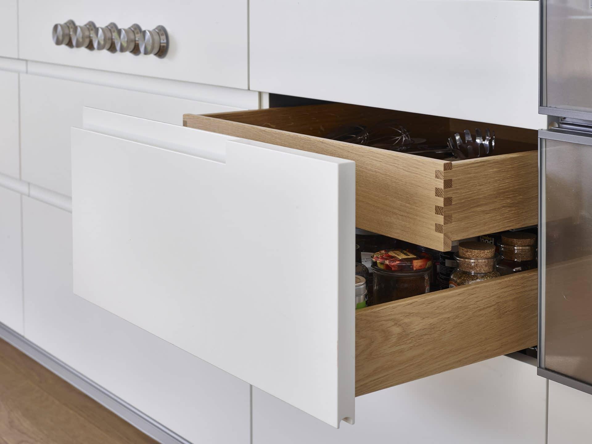 Inneneinrichtungsdesign von Voit, Küche mit weißen Fronten, Eiche natur - Geöffnete Schublade mit Gewürzen, im Hintergrund Kochfeld Regler
