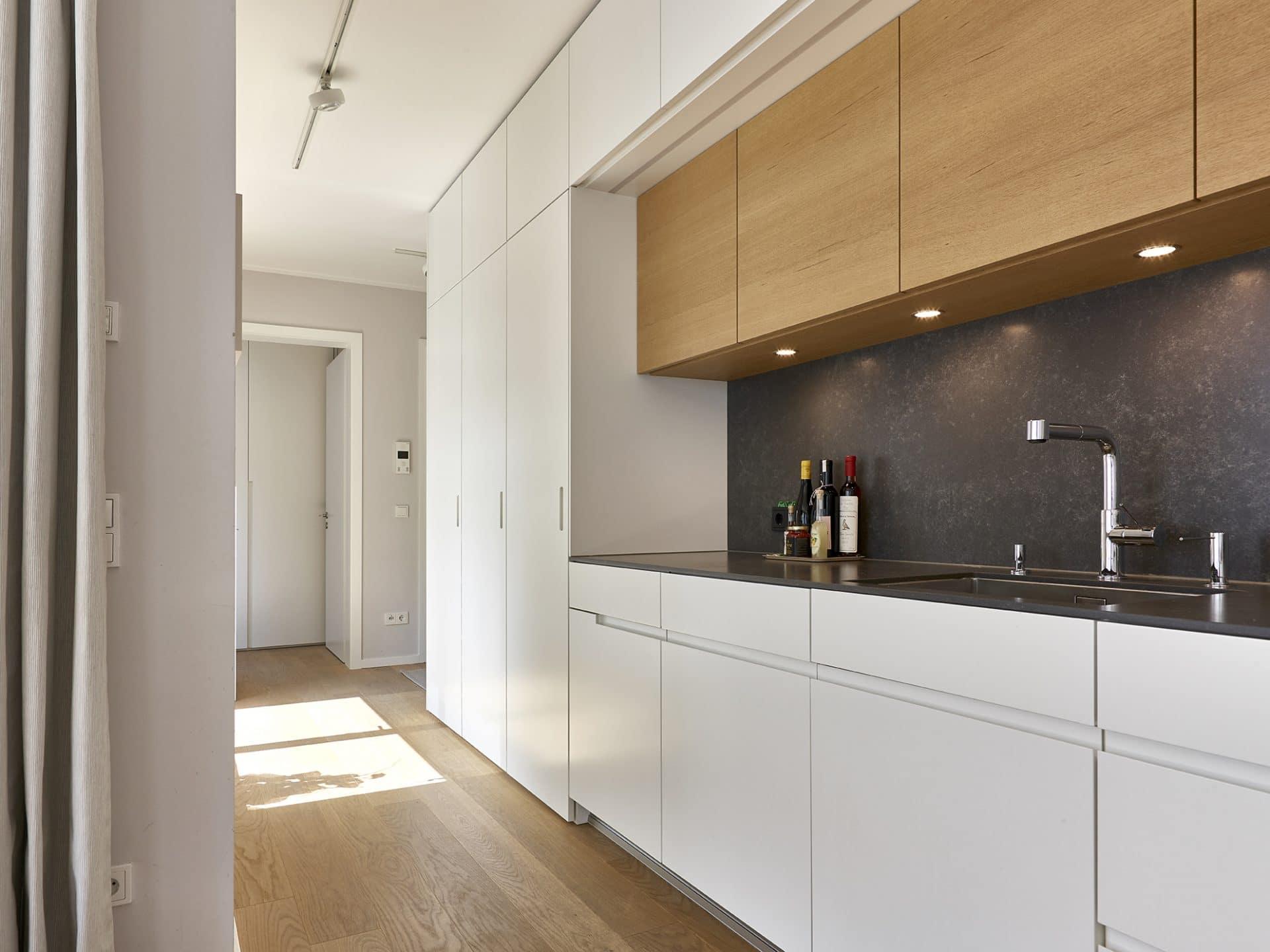 Inneneinrichtungsdesign von Voit, Küche mit weißen Fronten und schwarzer Arbeitsplatte, Eiche natur, BetonART, Mattlack weiß, Edelstahl als zusätzliche Materialien