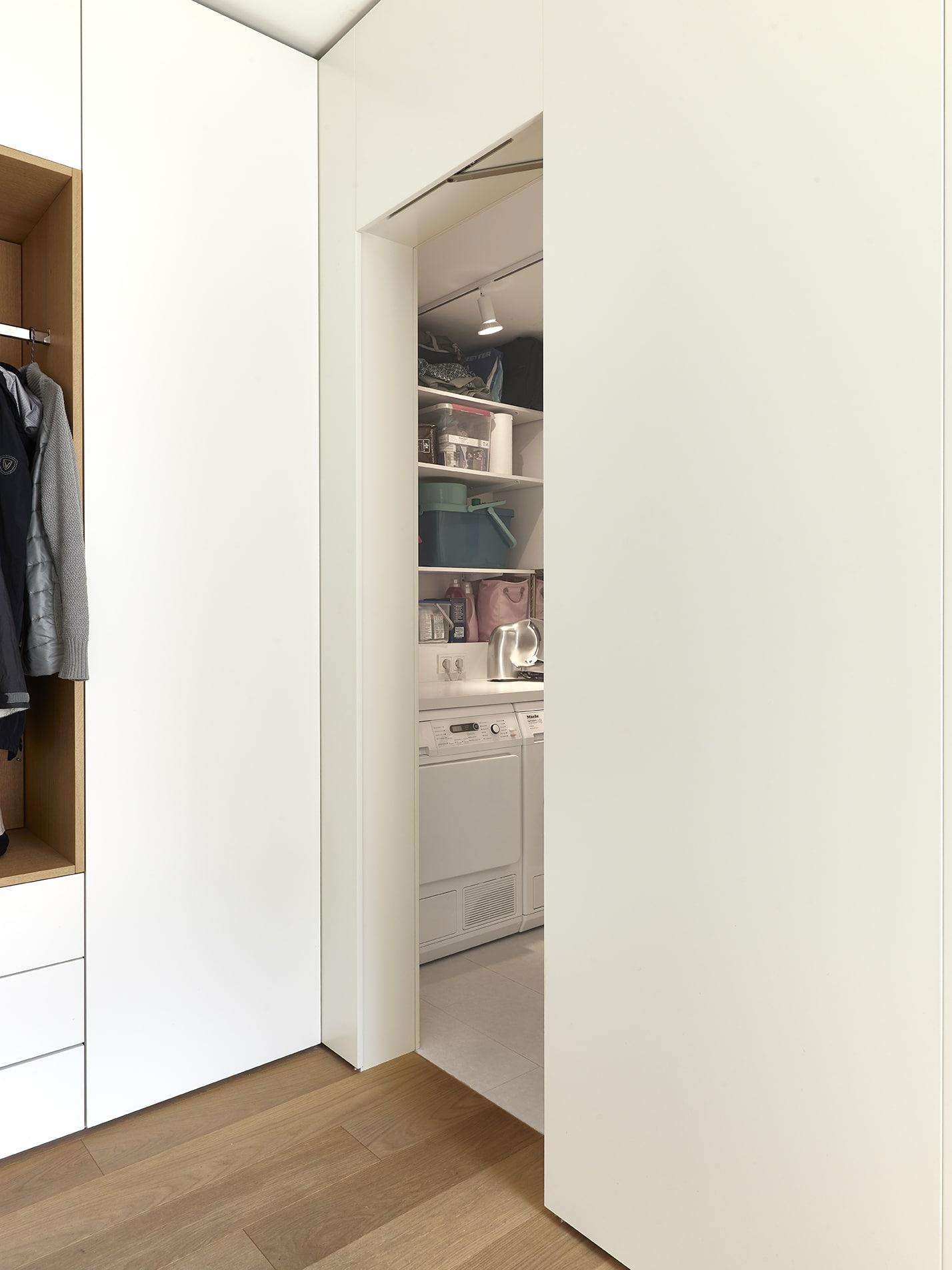 Inneneinrichtungsdesign von Voit, Küche mit weißen Fronten und schwarzer Arbeitsplatte, Eiche natur, BetonART, Mattlack weiß, Edelstahl als zusätzliche Materialien - Blick in die Waschküche mit Einbaulösungen