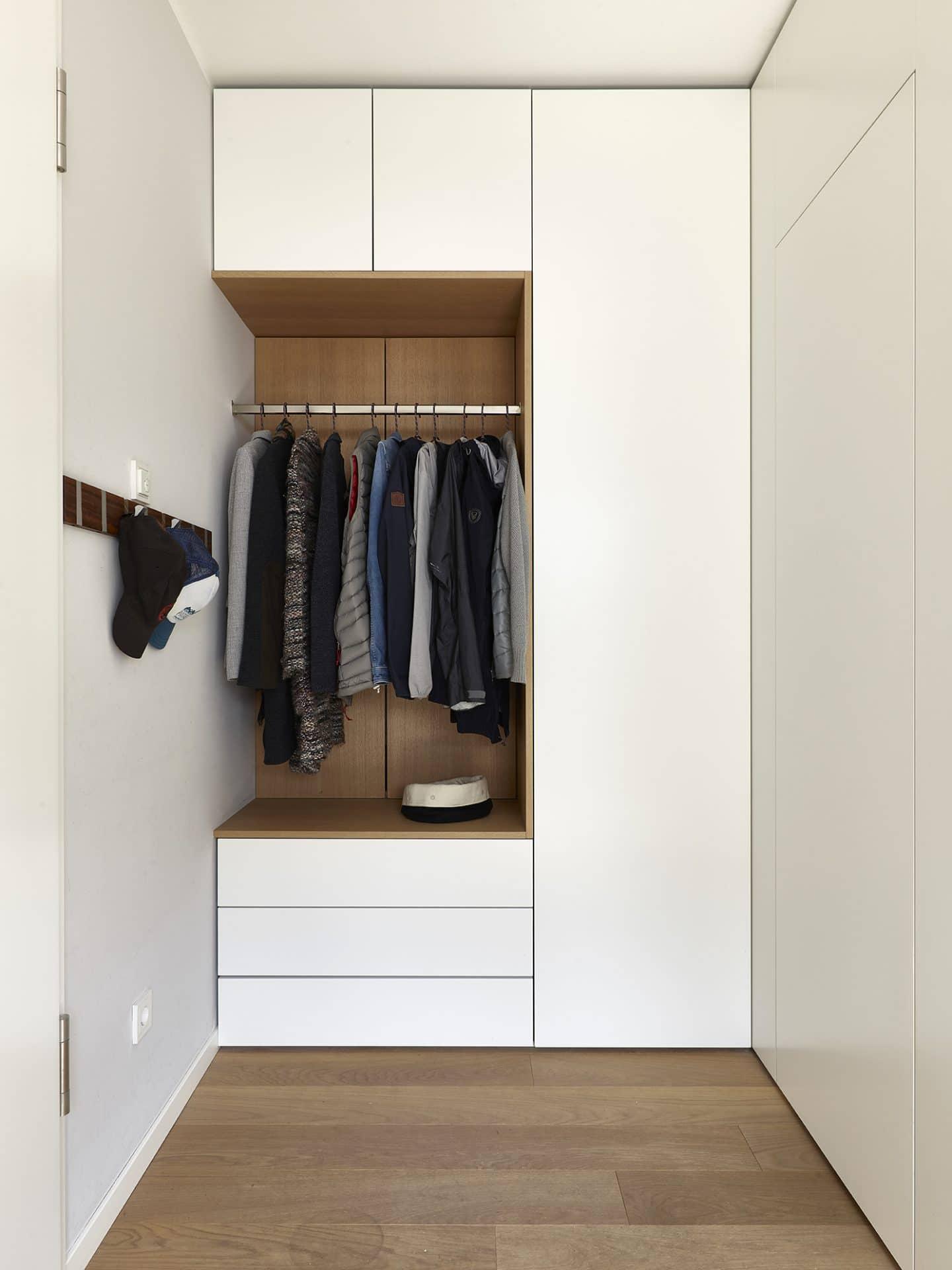 Inneneinrichtungsdesign von Voit, Küche mit weißen Fronten aus Eiche natur - Garderobe mit Kleidungsstücken