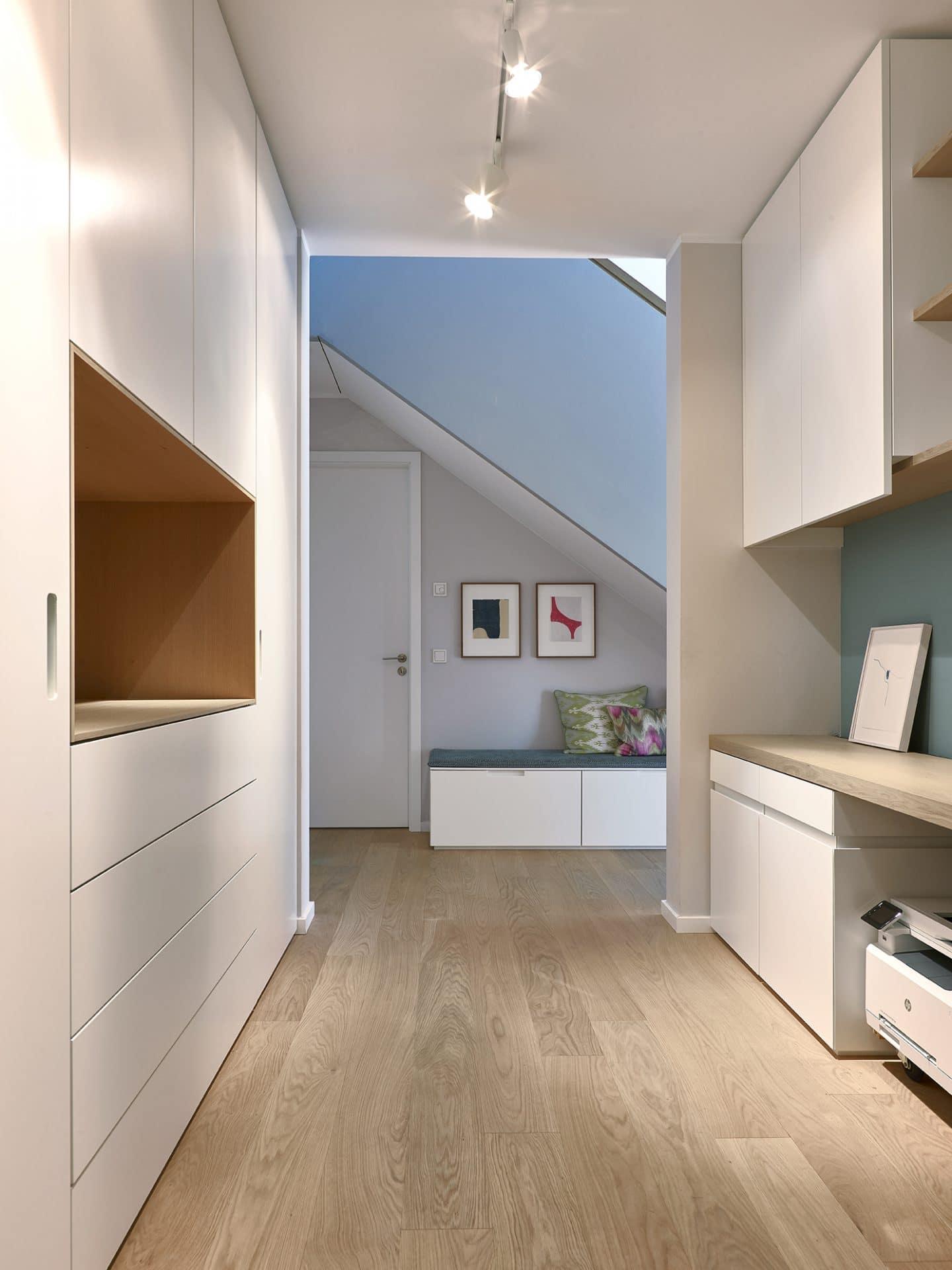 Inneneinrichtungsdesign von Voit, Küche aus Mattlack weiß - Blick in den Eingangsbereich mit Bank