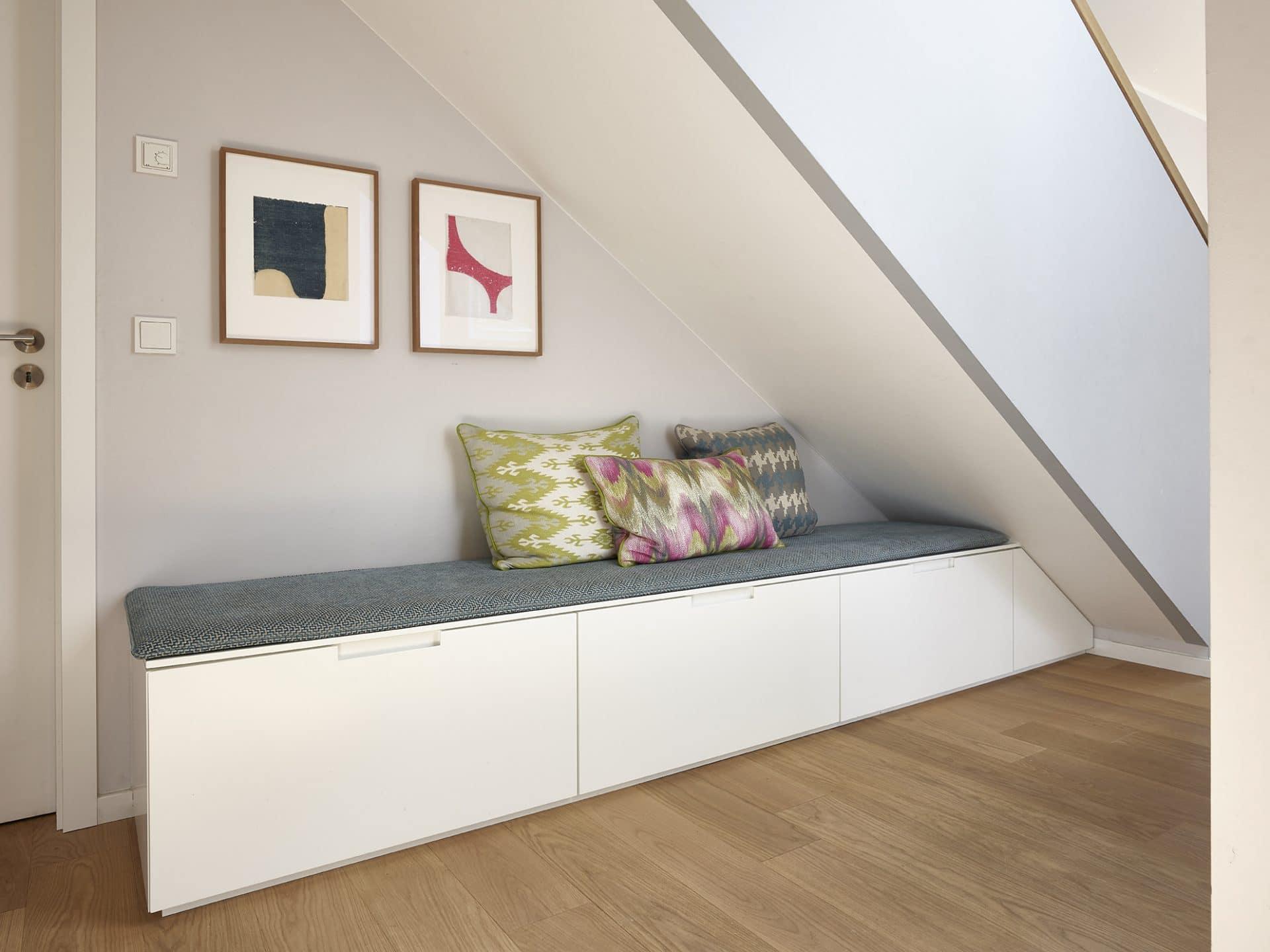 Inneneinrichtungsdesign von Voit, Küche aus Mattlack weiß - Blick in den Eingangsbereich mit Bank unter einer Treppe