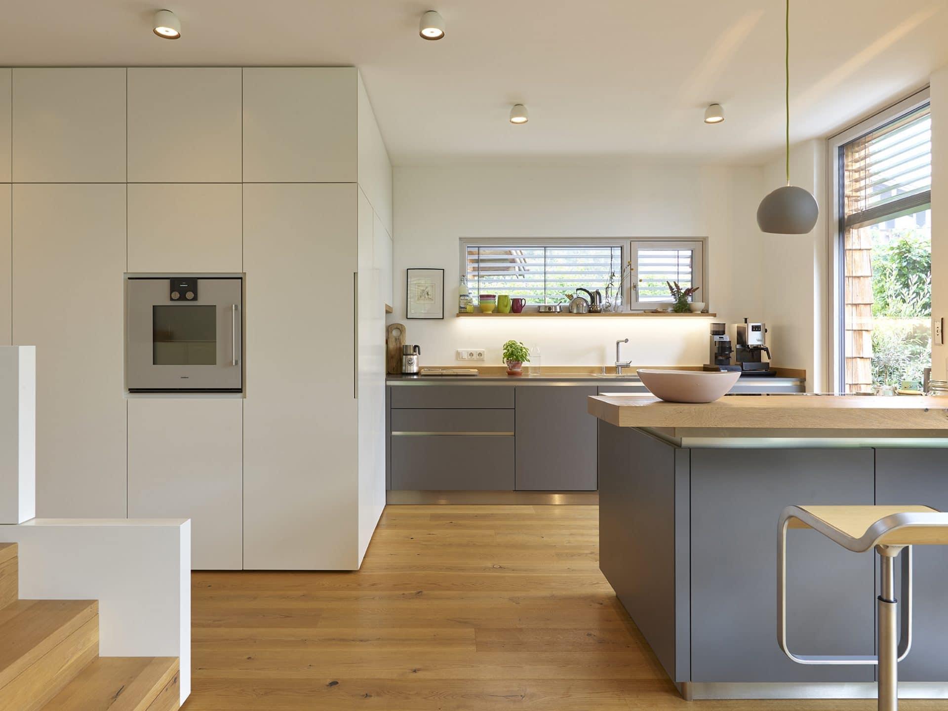 Küchendesign von VOIT in Eiche Natur mit BetonART und Edelstahl - Weiß graue Fronten und Naturarbeitsplatte aus Eiche.