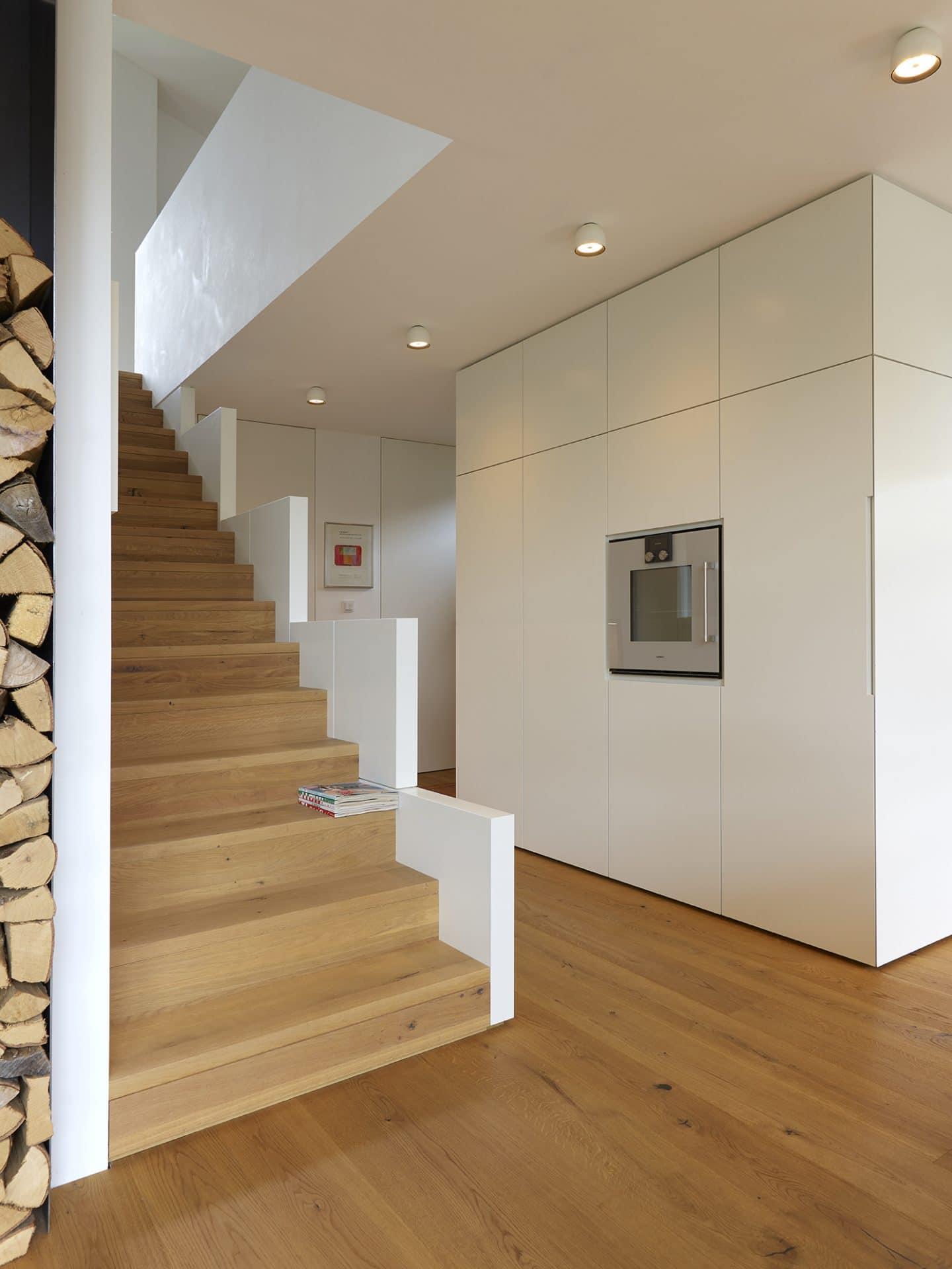 Küchendesign von VOIT in Eiche Natur mit BetonART und Edelstahl - Einbaugerät, links Holztreppe